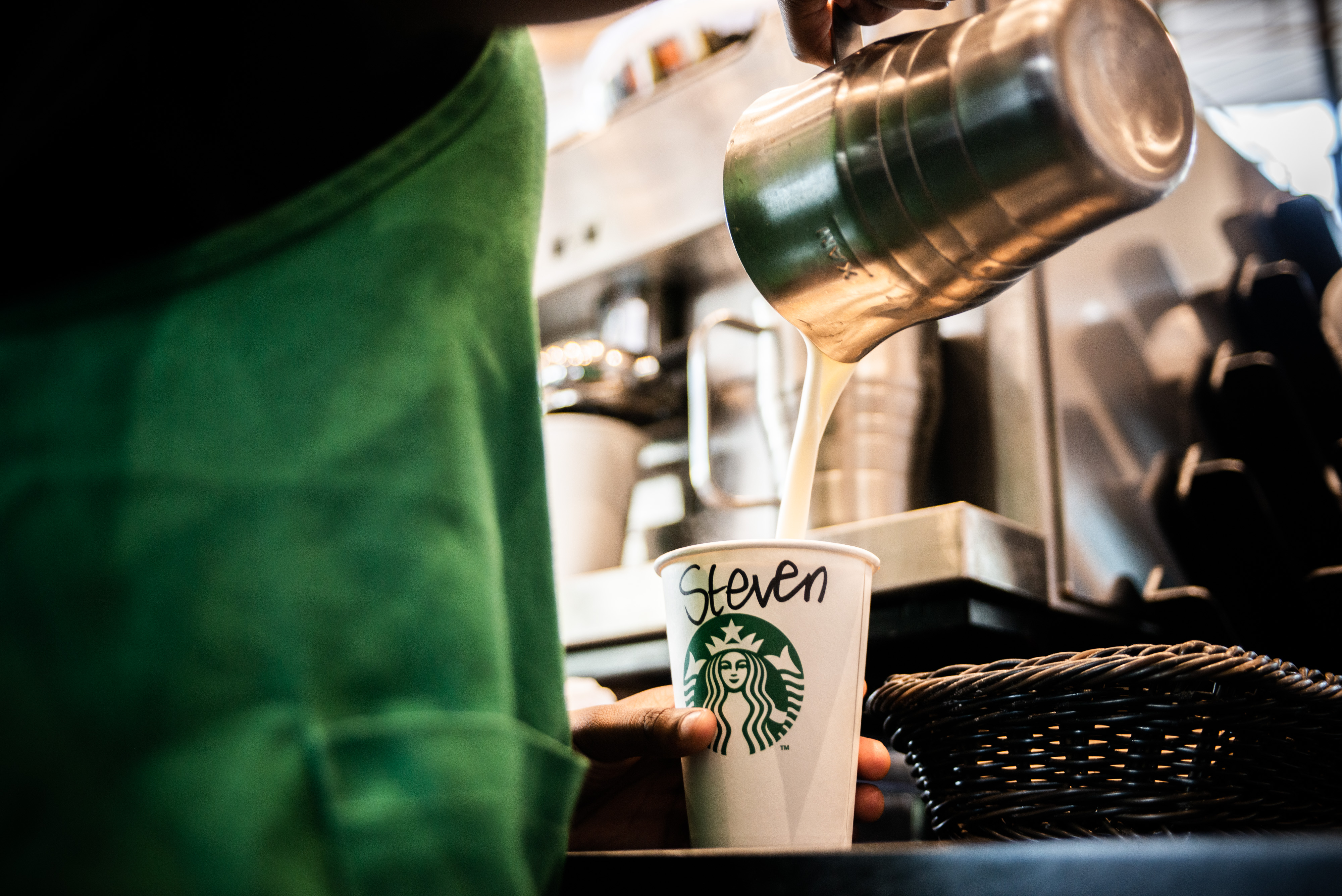 A person in a green apron pours milk from a pitcher into a white Starbucks to-go cup