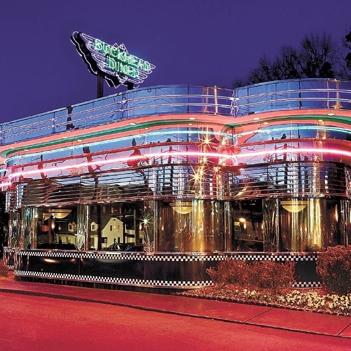 The silver chrome of the exterior of Buckhead Diner in Atlanta glows against the red, orange, and blue of the neon lights wrapping the restaurant building