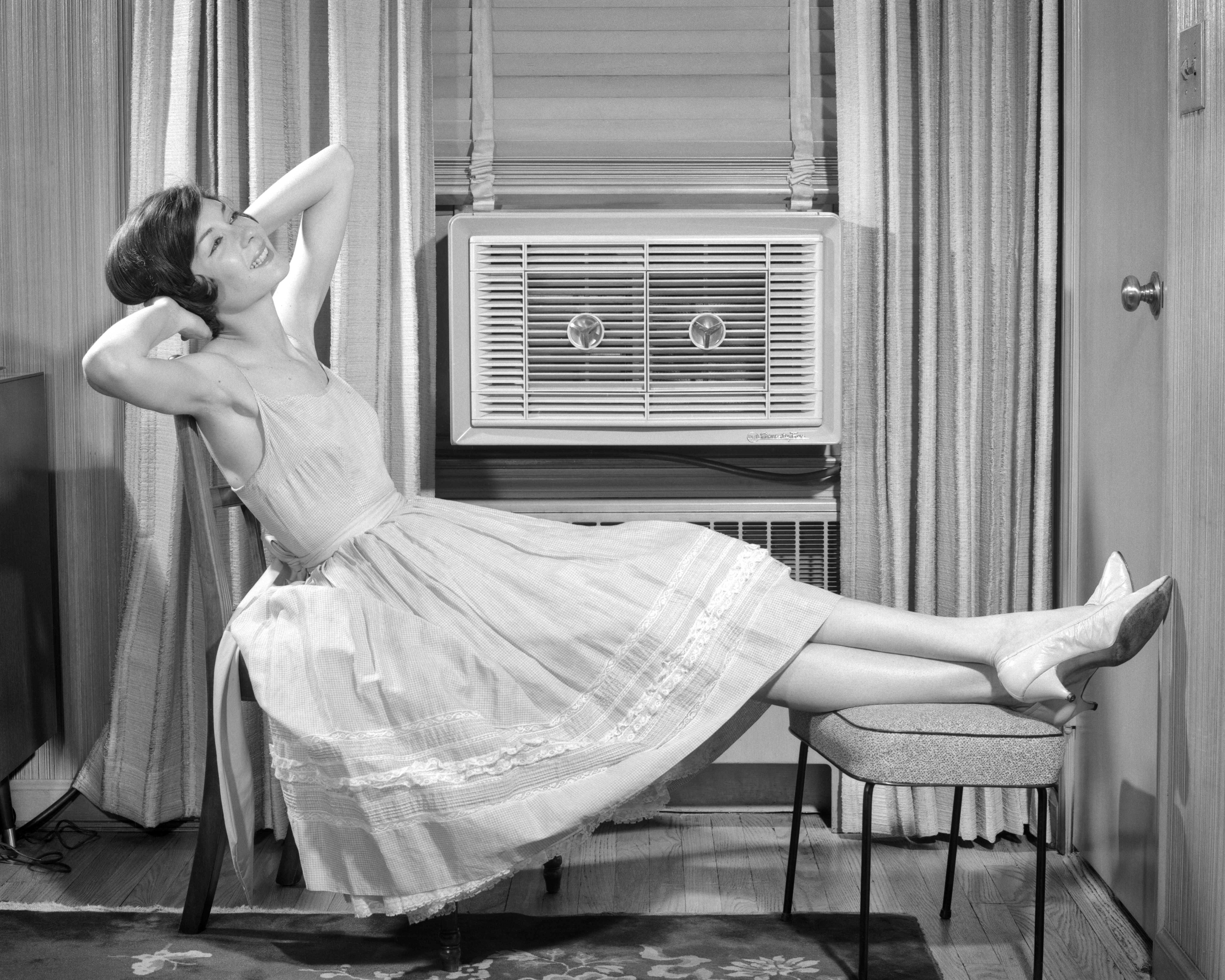 A vintage photo of a woman relaxing in front of a window-mounted air conditioner in her home.