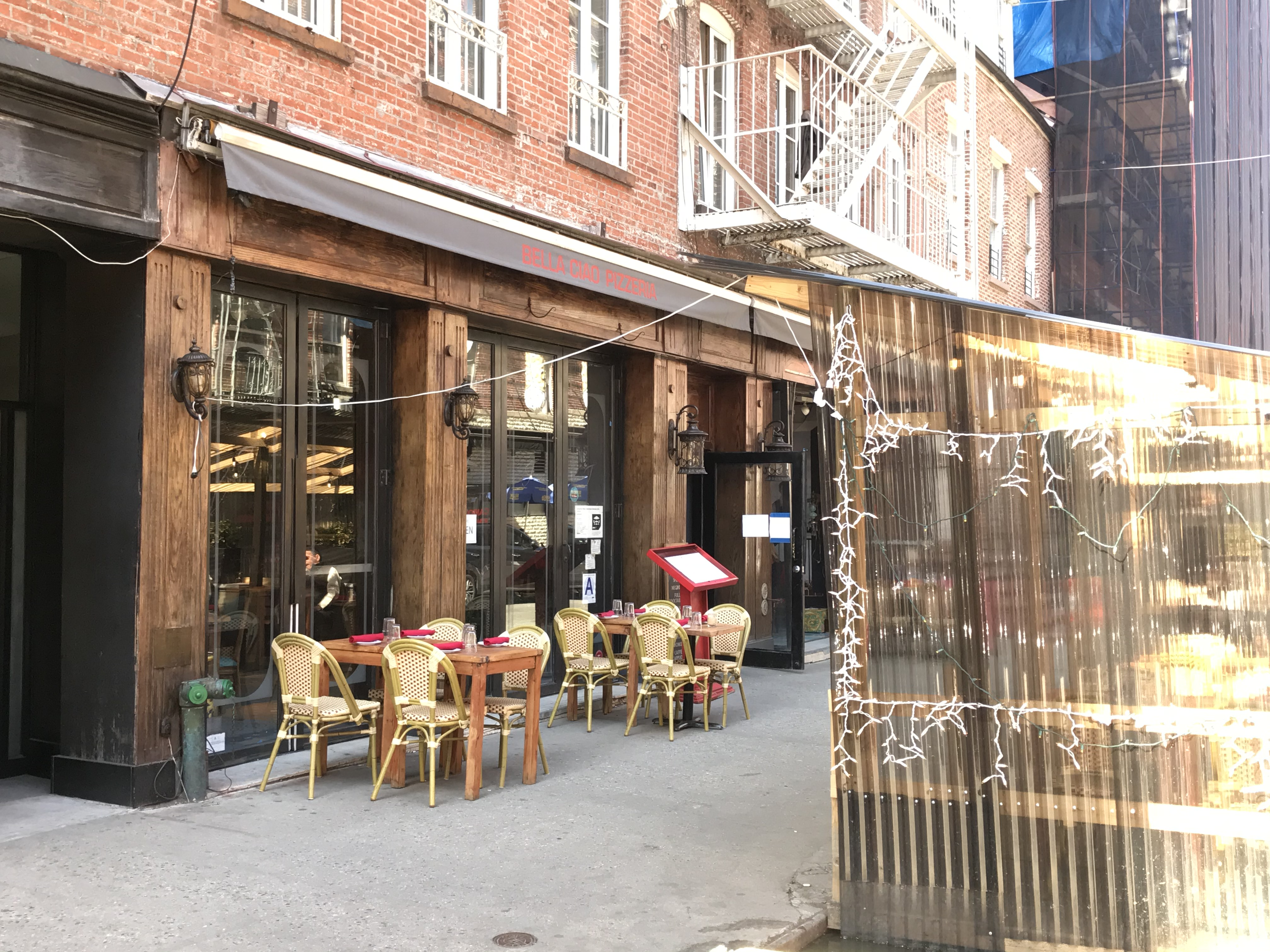 """A few wooden tables and an outdoor dining structure sit in front of a restaurant with an awning that reads """"Bella Ciao"""""""