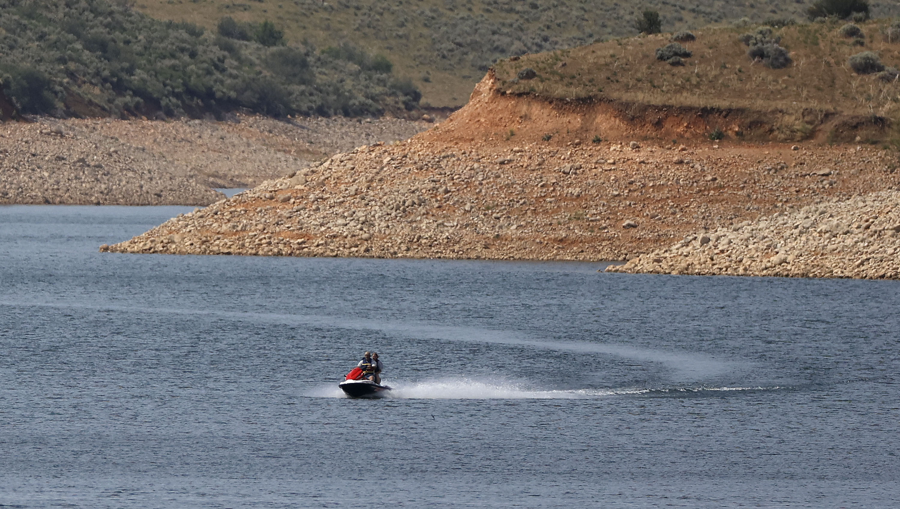 Low water levels are visible as a person rides a personal watercraft on East Canyon Reservoir in Morgan County during a drought in Utah on Wednesday, June 16, 2021.