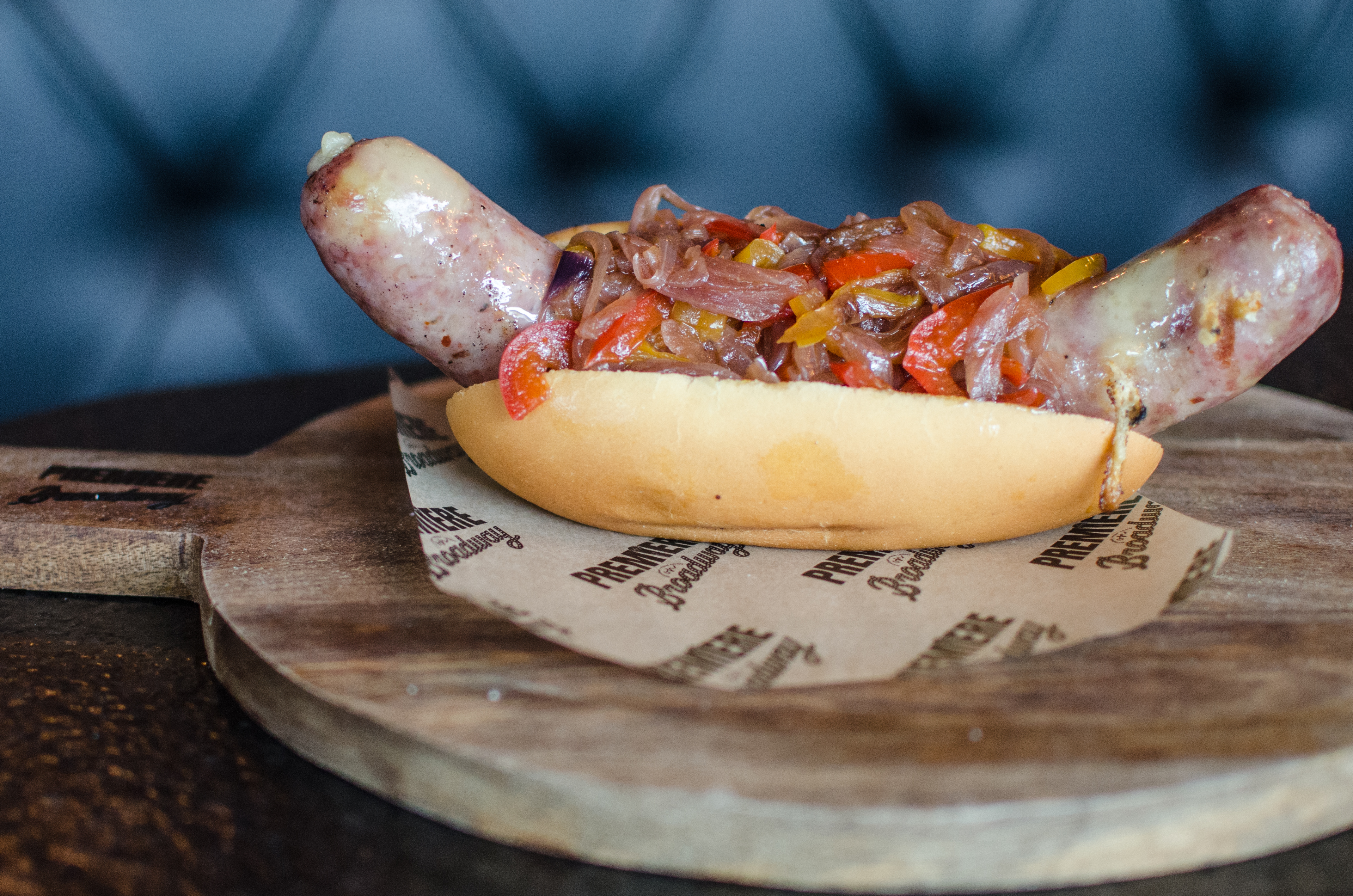A fat, rounded sausage with melted cheese dripping from the ends sits in a small potato bun and is topped with sauteed peppers and onions. The whole thing sits on a round wooden board with a handle; Premiere on Broadway is branded onto the handle. The board is on a black table with a dark teal booth visible in the background.
