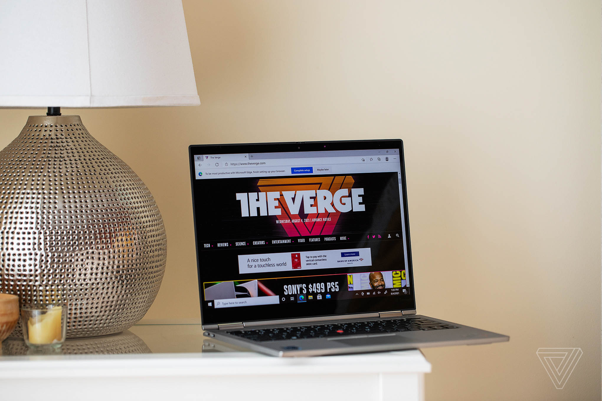 The Lenovo ThinkPad X1 Titanium Yoga open on a bedside table next to a lamp, angled to the right. The screen displays The Verge's homepage.