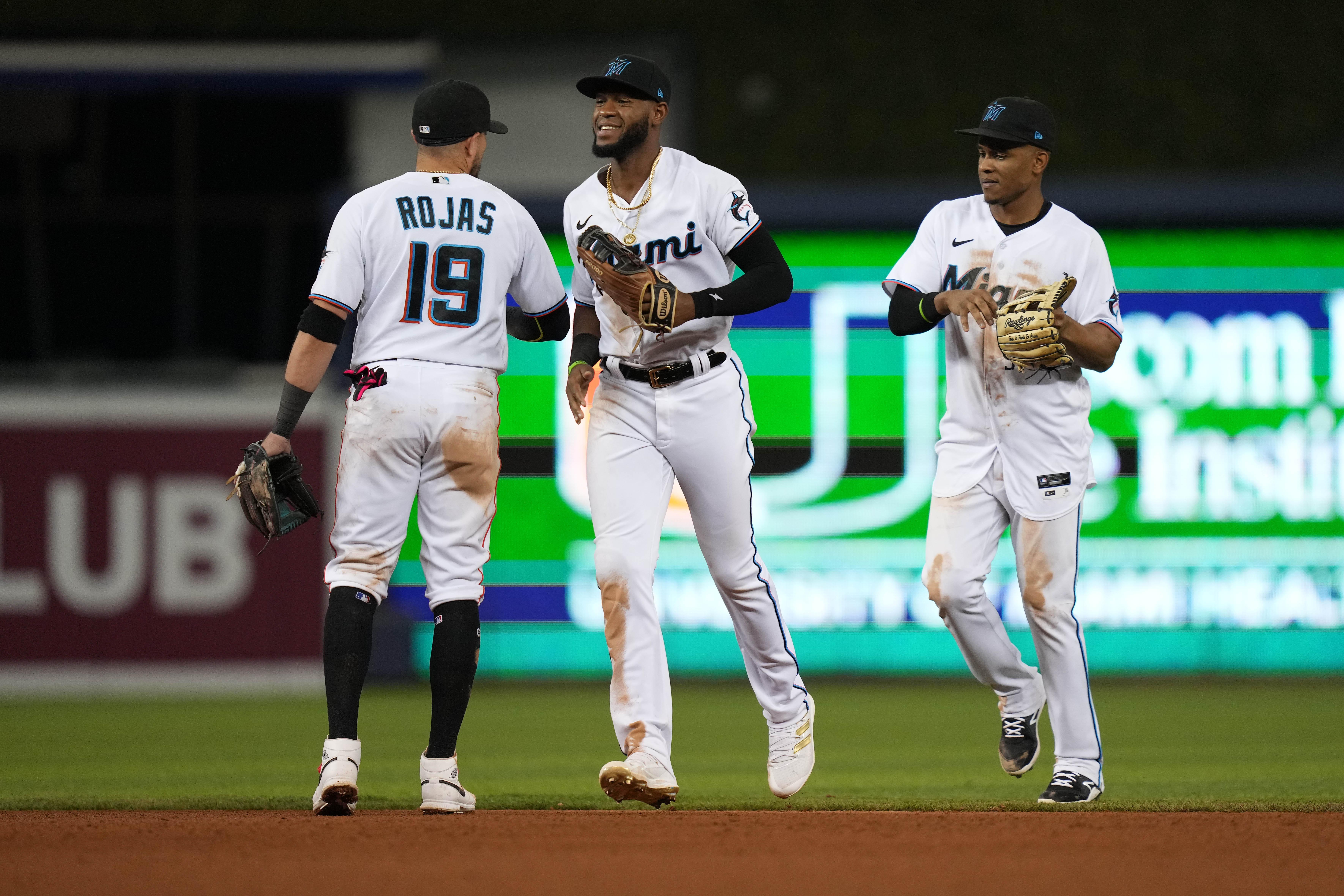 Miami Marlins shortstop Miguel Rojas (19), left fielder Bryan De La Cruz (77) and center fielder Magneuris Sierra (34) celebrate after defeating the Washington Nationals at loanDepot park