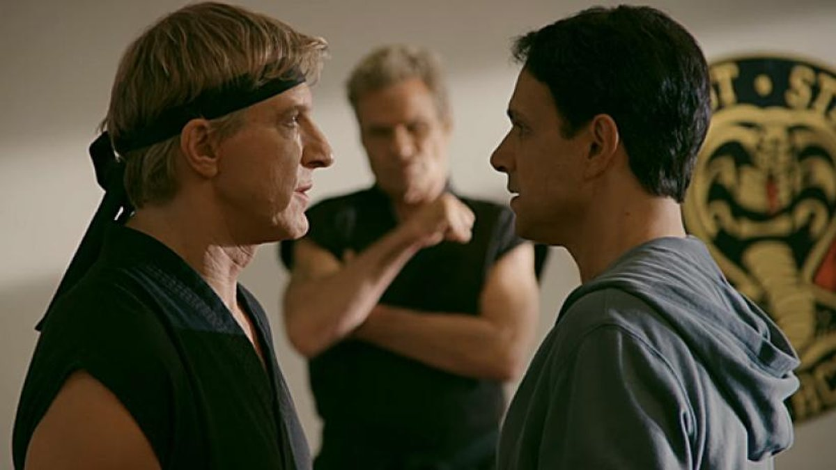 Johnny and Daniel face off with Kreese in the background in a still from Cobra Kai