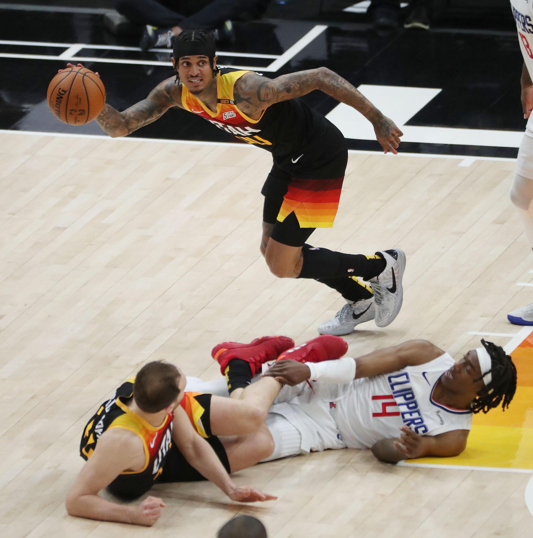 Utah Jazz guard Jordan Clarkson dribbles around Clippers guard Terance Mann during NBA playoffs in Salt Lake City.