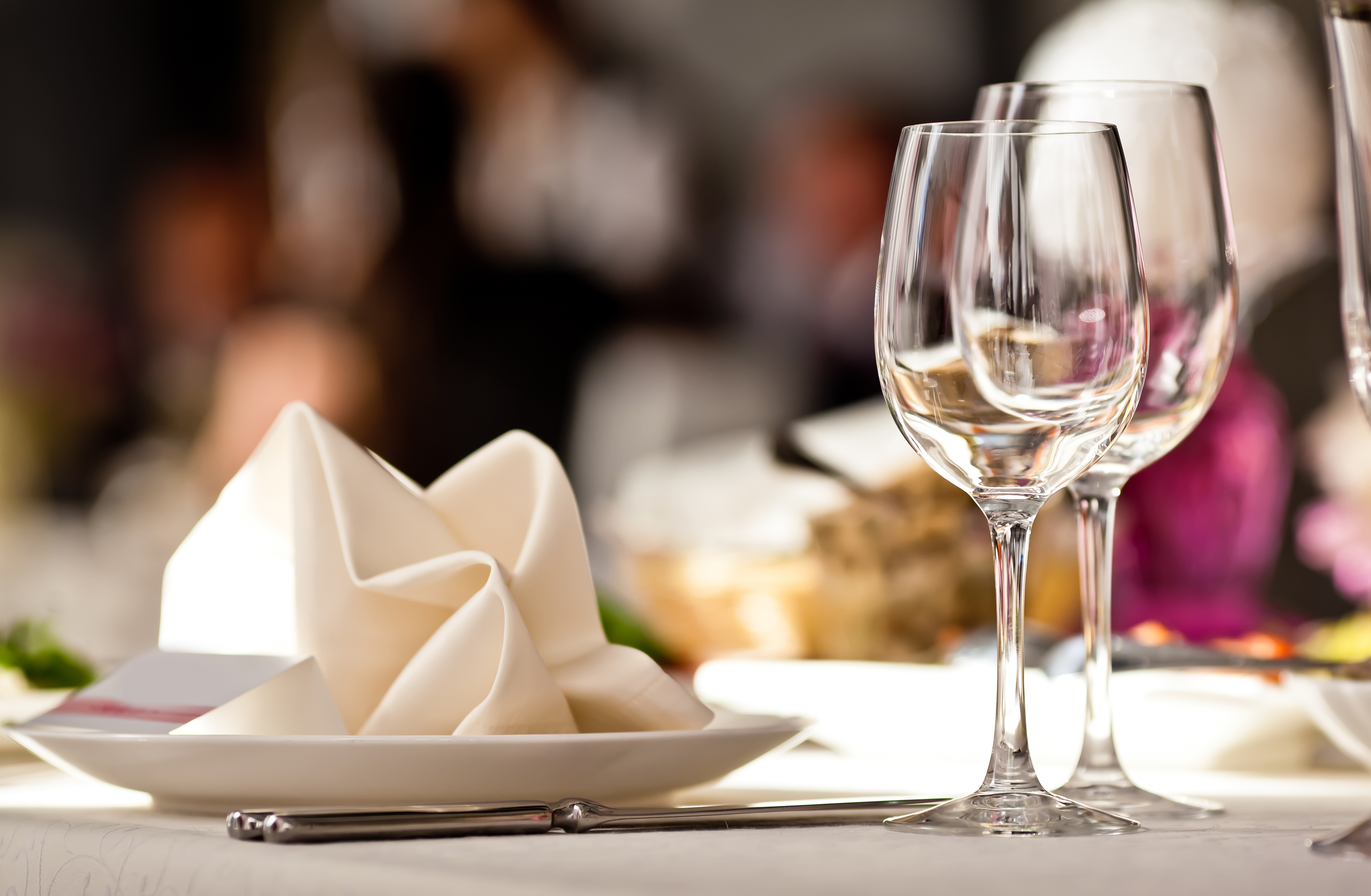 Two wine glasses next to a plate with a napkin on top at a restaurant.