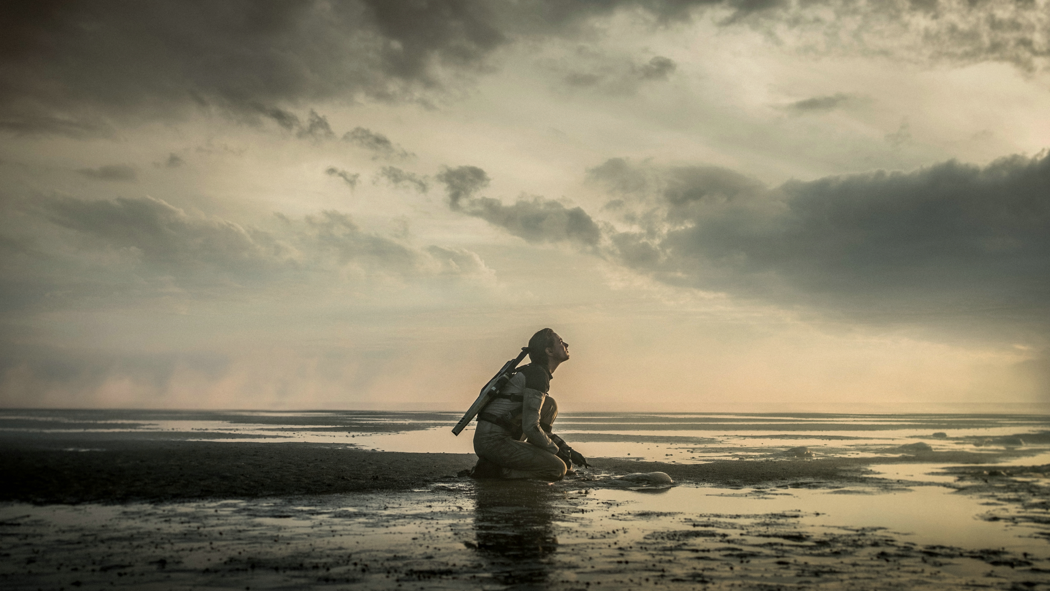 A female figure kneeling in the water by the shore in a yellow-tinged landscape in The Colony