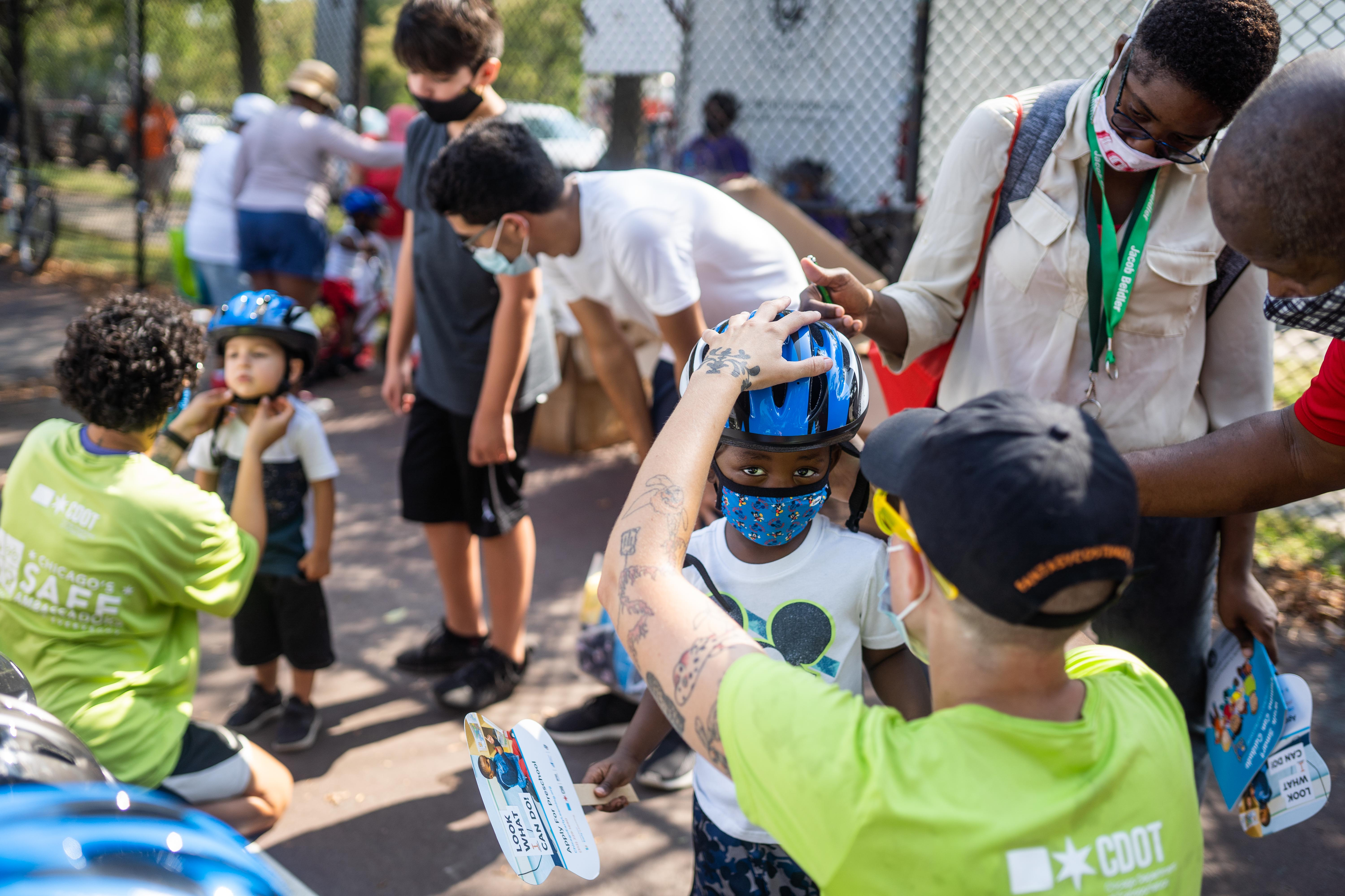 Dylan Jackson gets fitted for a helmet during a bike giveaway and safety camp event at Union Park Saturday morning.