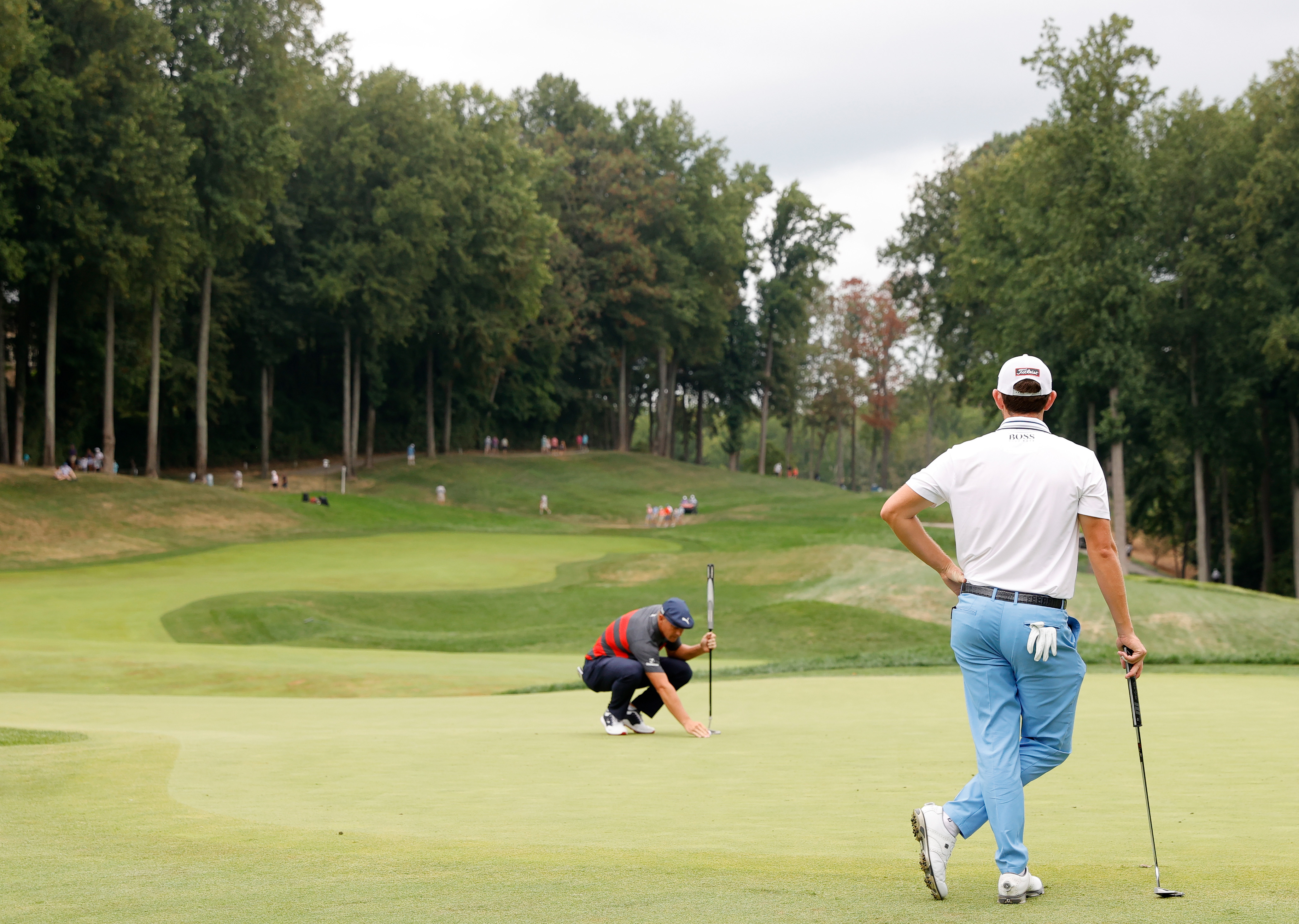 Bryson DeChambeau of the United States lines up a putt as Patrick Cantlay of the United States looks on during the final round of the BMW Championship at Caves Valley Golf Club on August 29, 2021 in Owings Mills, Maryland.