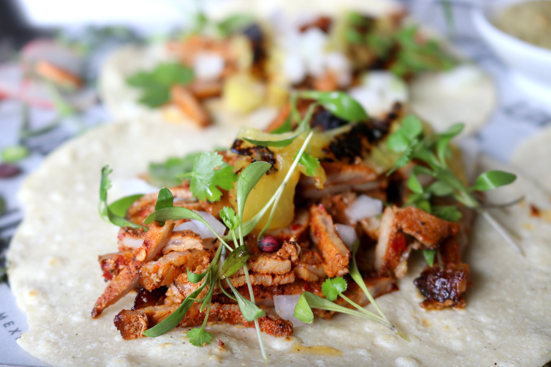 Pork al pastor and microgreen garnish sitting on top of a white flour tortilla