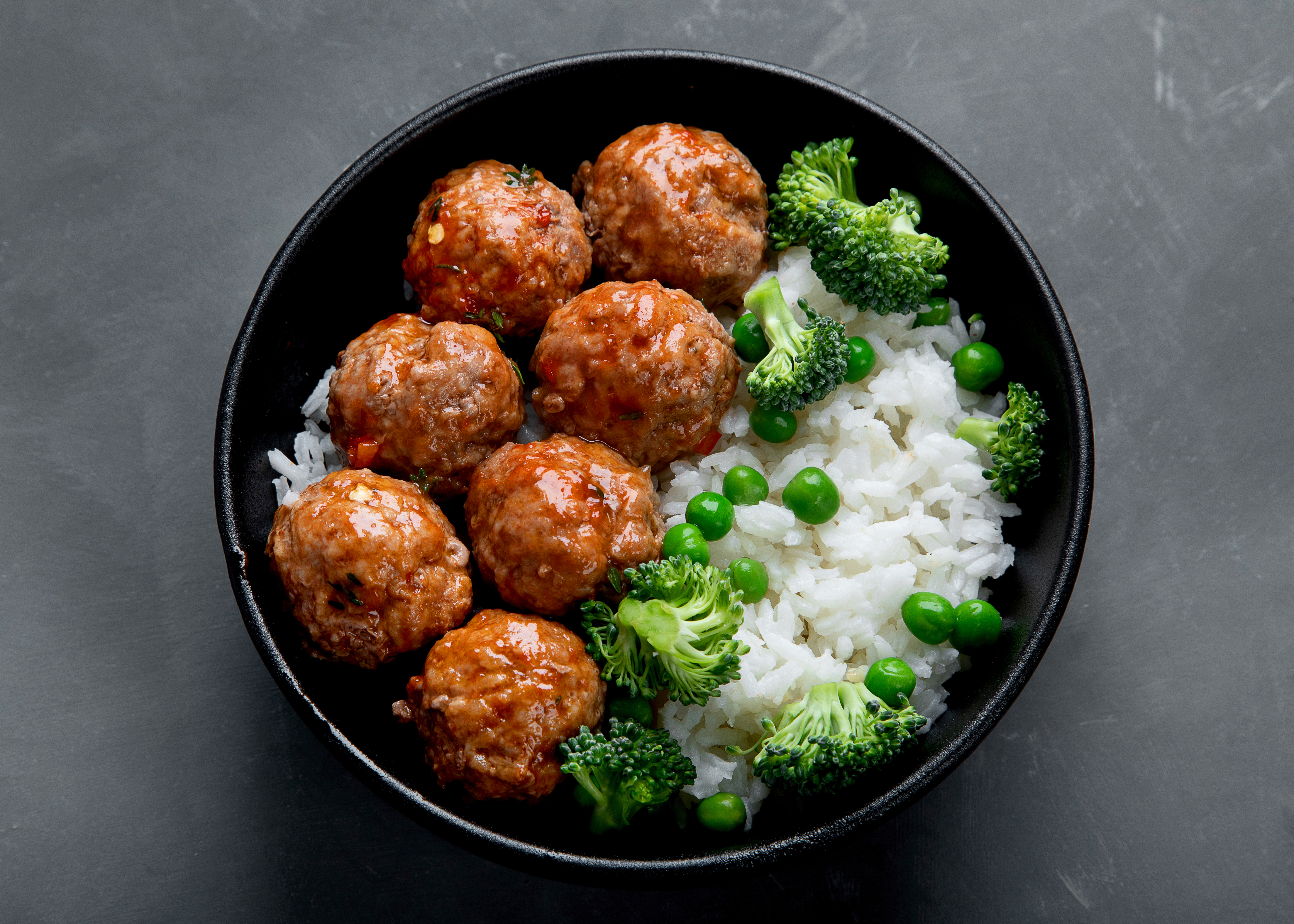 Seven meatballs in a black bowl sit alongside white rice, broccoli, and peas.