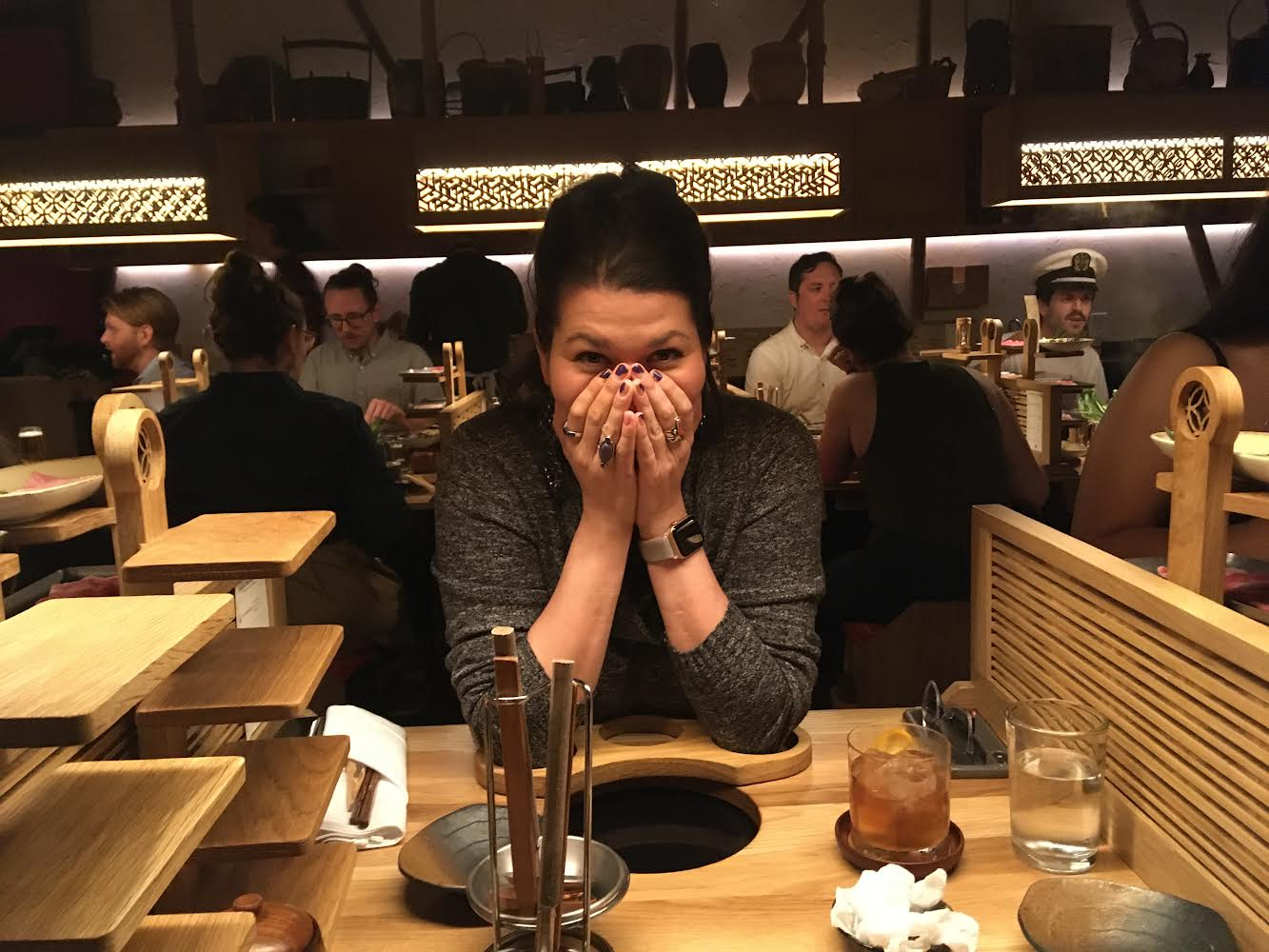 A woman sitting at a restaurant table with hands on her face
