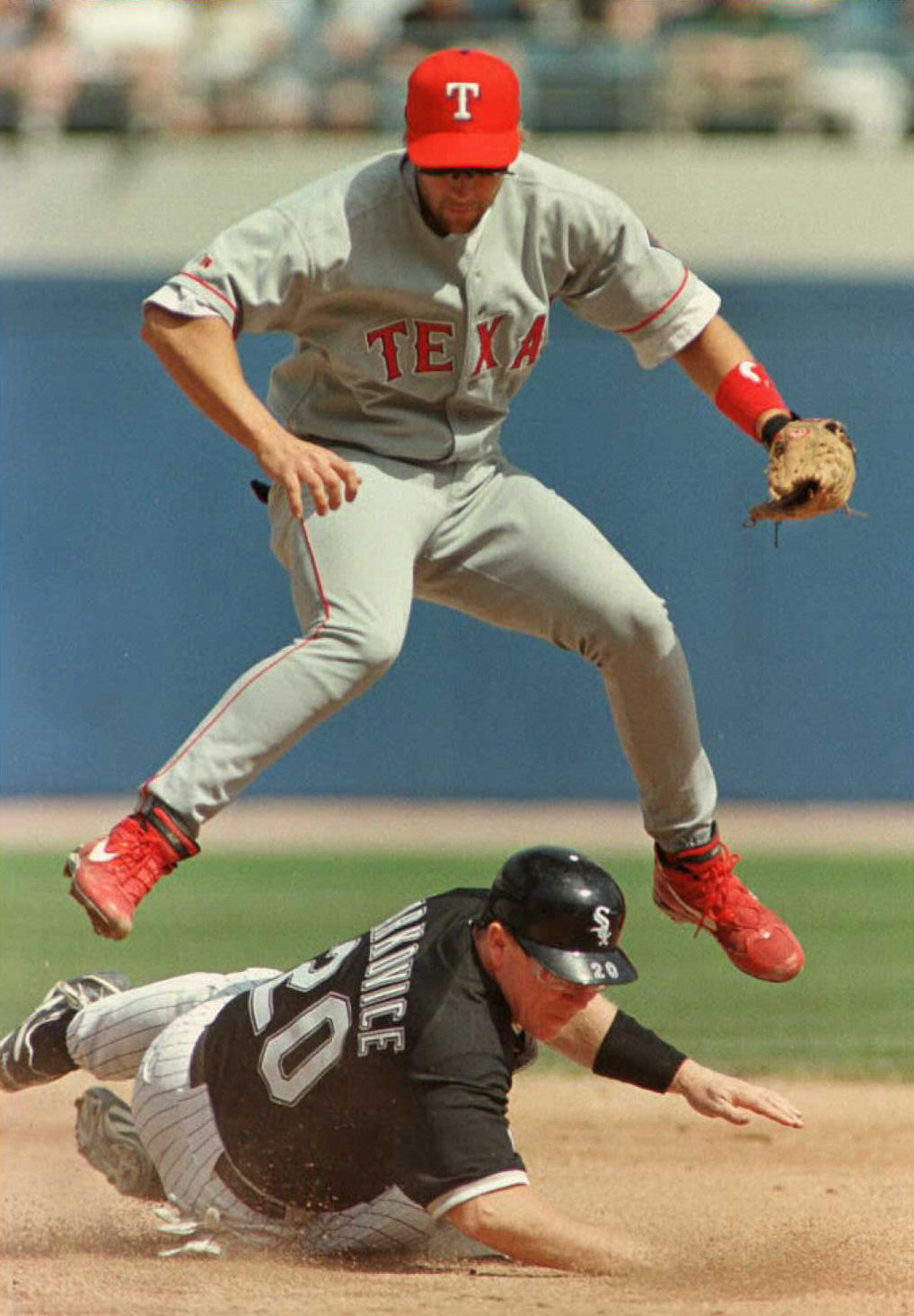 Texas Rangers shortstop Kevin Elster jumps to avoi