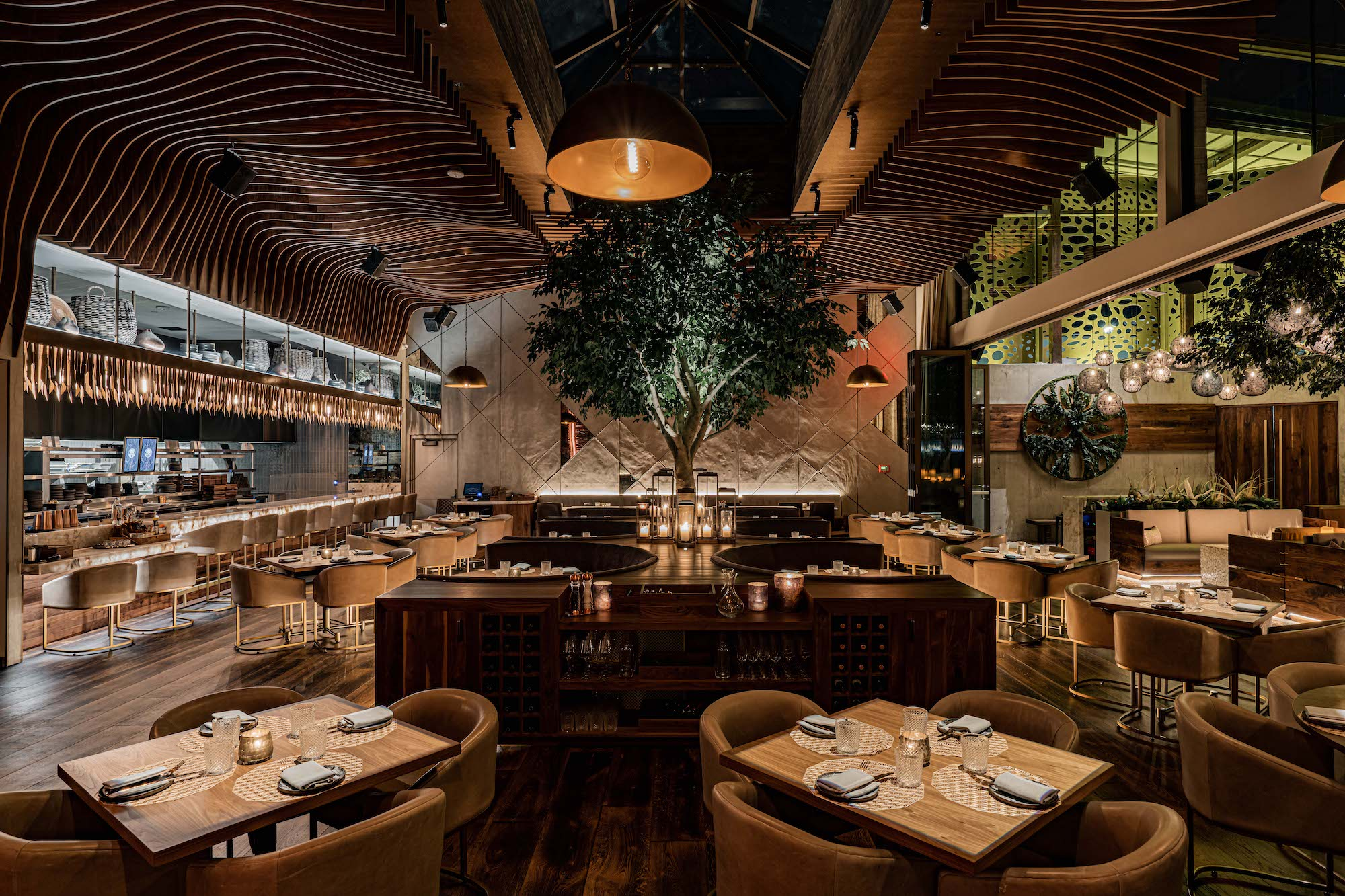 A restaurant dining room with a tree in the middle