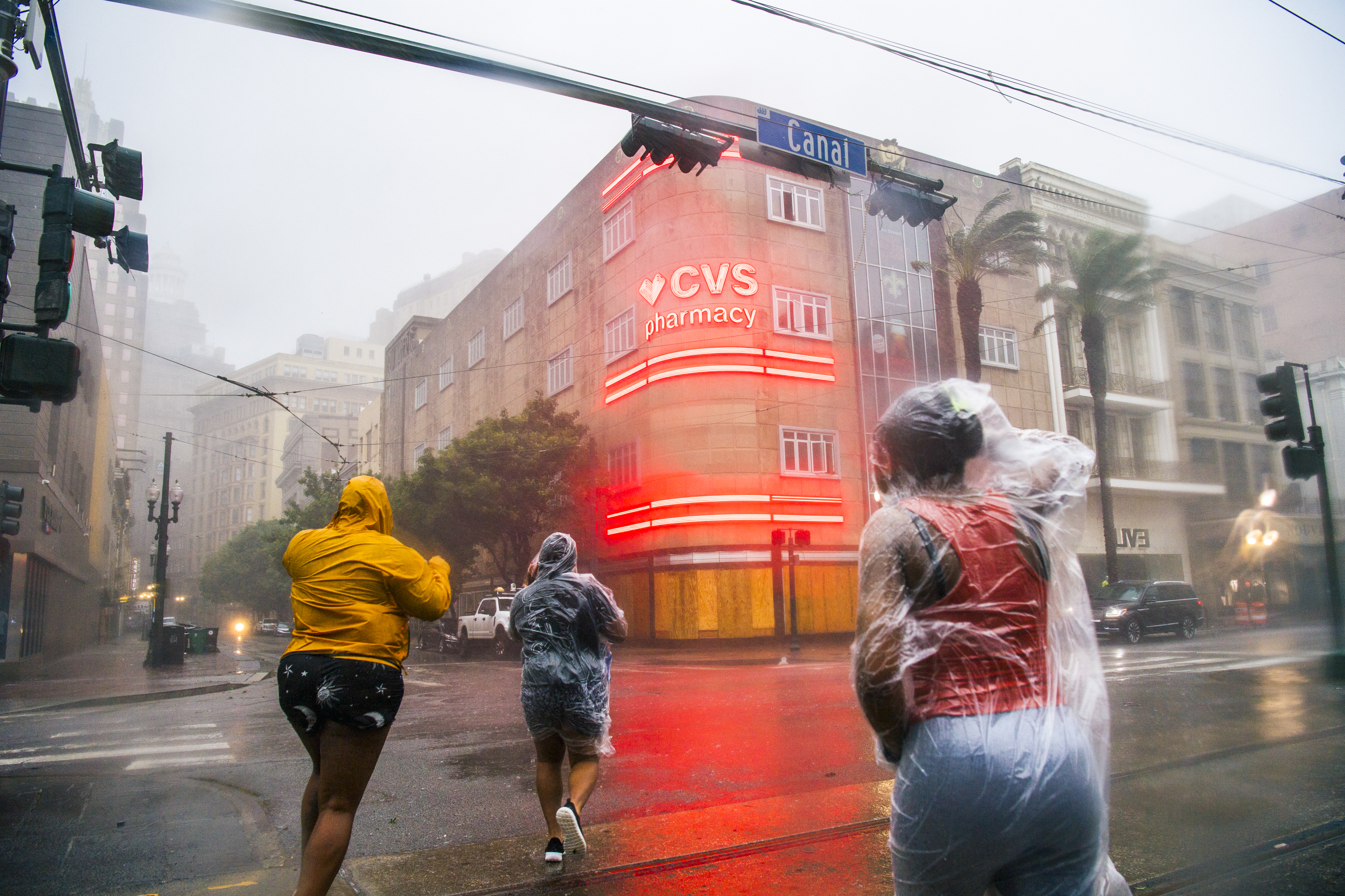 People run across a street in New Orleans in the rain and wind.
