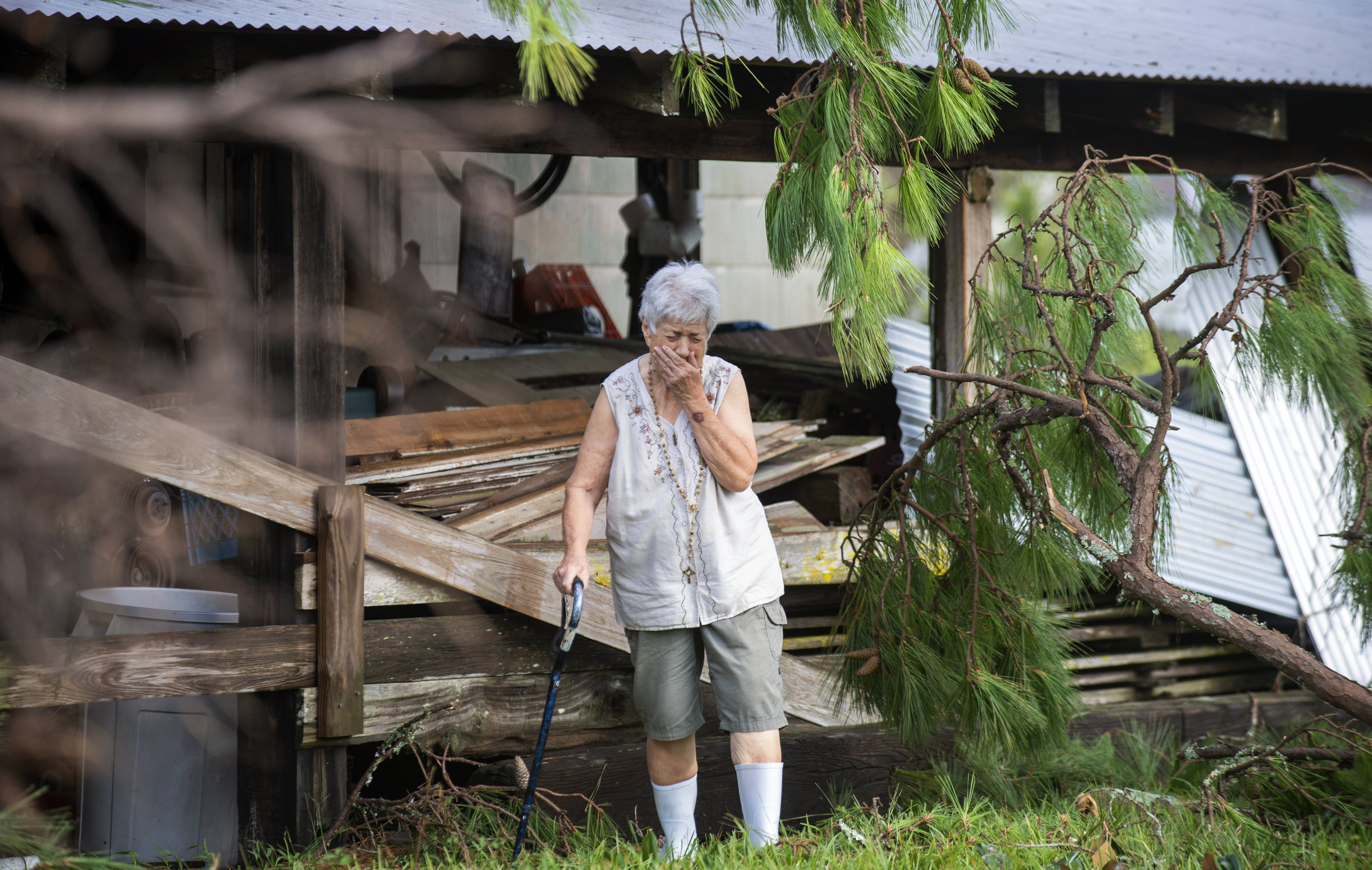 Sharon Orlando tries to hold back tears while surveying the damage from Hurricane Ida at her home in Destrehan, La.,