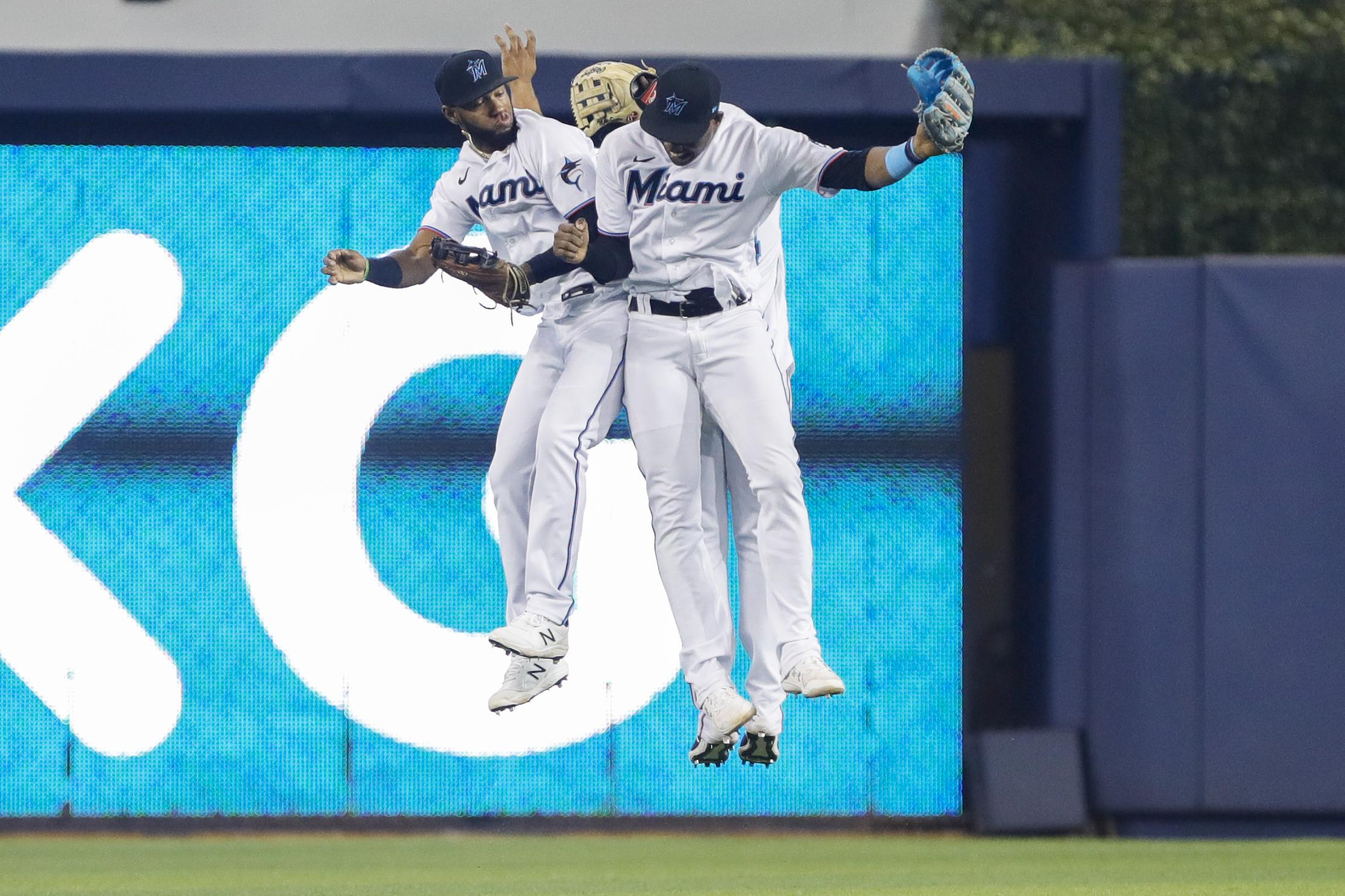 Miami Marlins right fielder Bryan De La Cruz (77) and right fielder Jesus Sanchez (76) celebrate after winning the game against the Cincinnati Reds at loanDepot Park