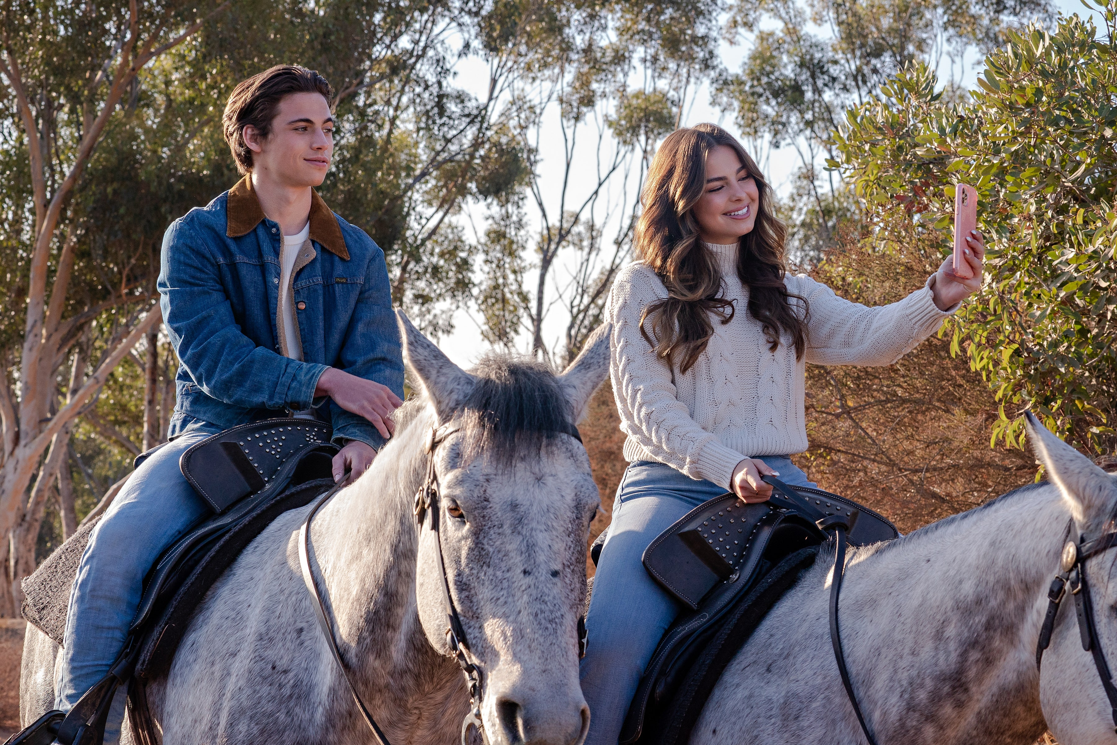 Two people ride on horseback while one takes a selfie.