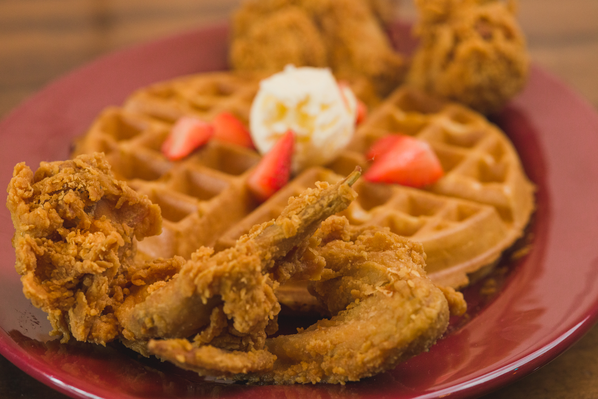 Chicken and waffles with strawberries and a pat of butter atop