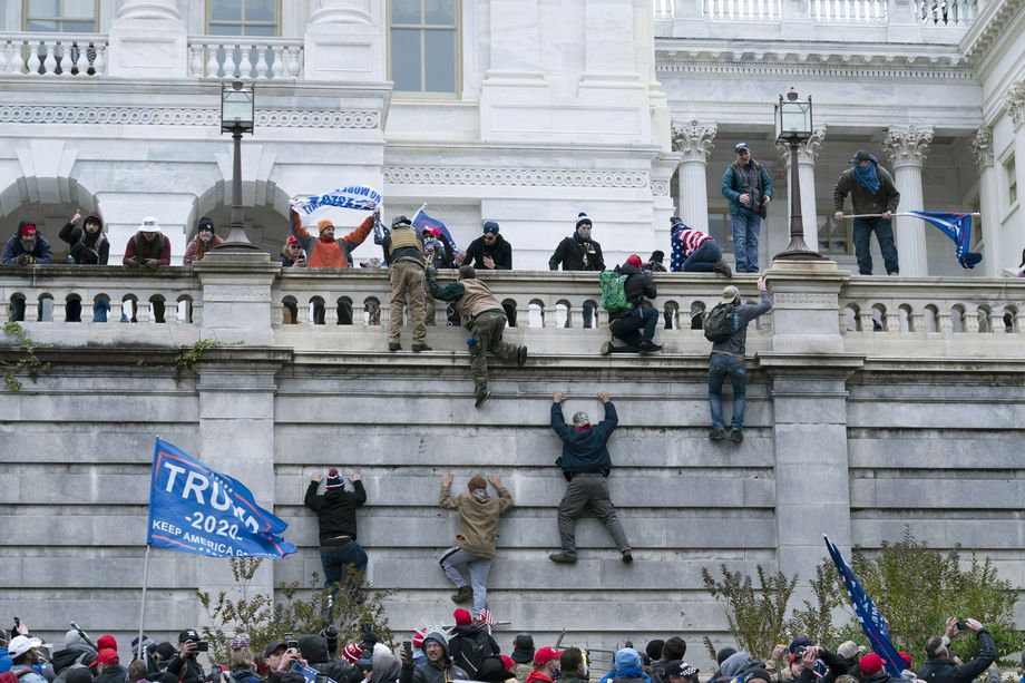 Supporters of President Donald Trump climb the west wall of the U.S. Capitol on Jan. 6.