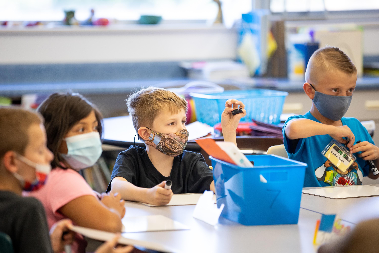 Josh Bird, Leslie Mancilla, Kaiden Smolka and Kingston Pedokie wear masks in their third grade class at Nibley Park School.