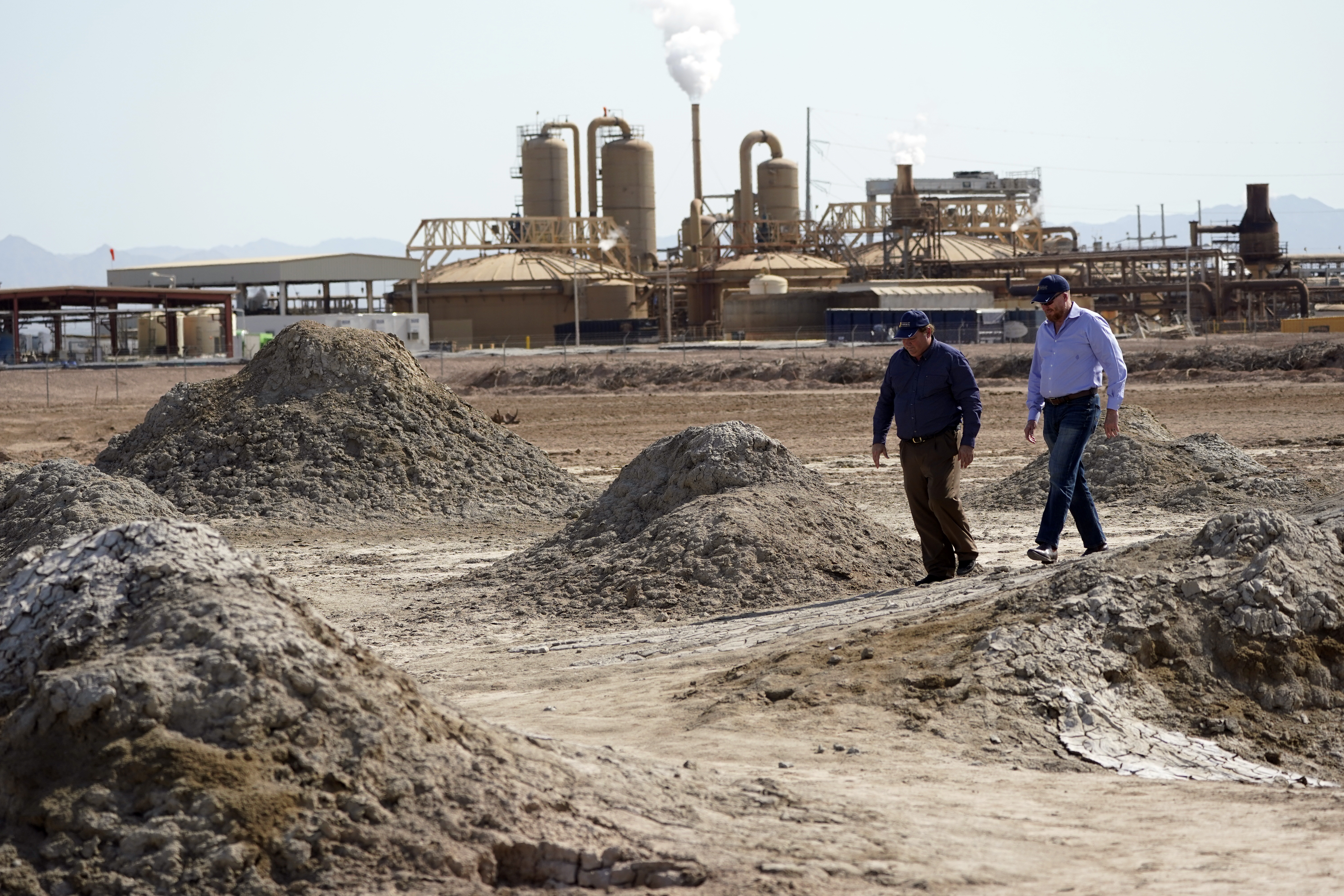 Rod Colwell (right), CEO of Controlled Thermal Resources, and Tracy Sizemore, the company's global director of battery materials, walk along geothermal mud pots near the shore of the Salton Sea, where the company is mining lithium from geothermal wastewater around the dying body of water. The ultralight metal is critical to rechargeable batteries.