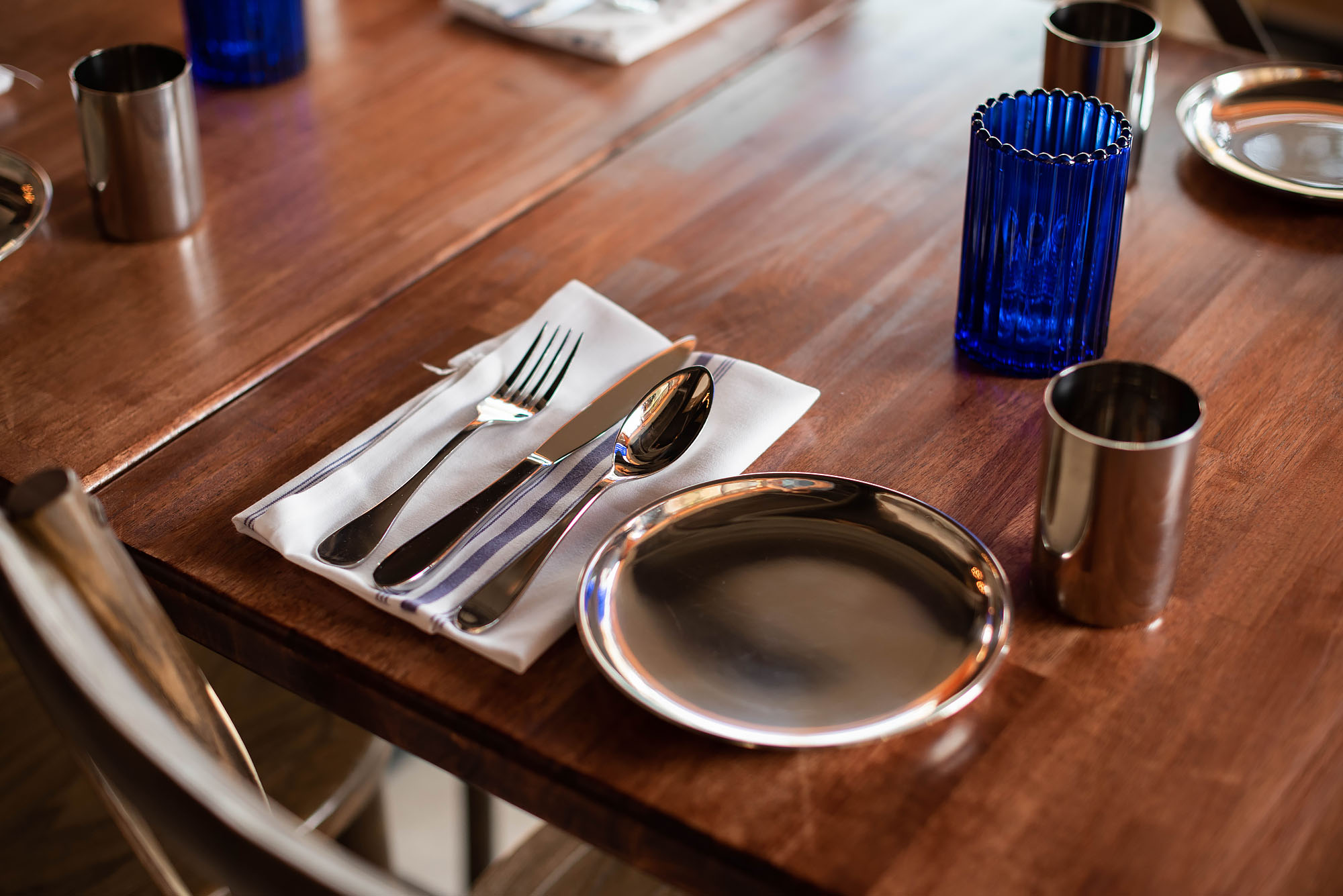 Simple metal plates on a wooden restaurant table.
