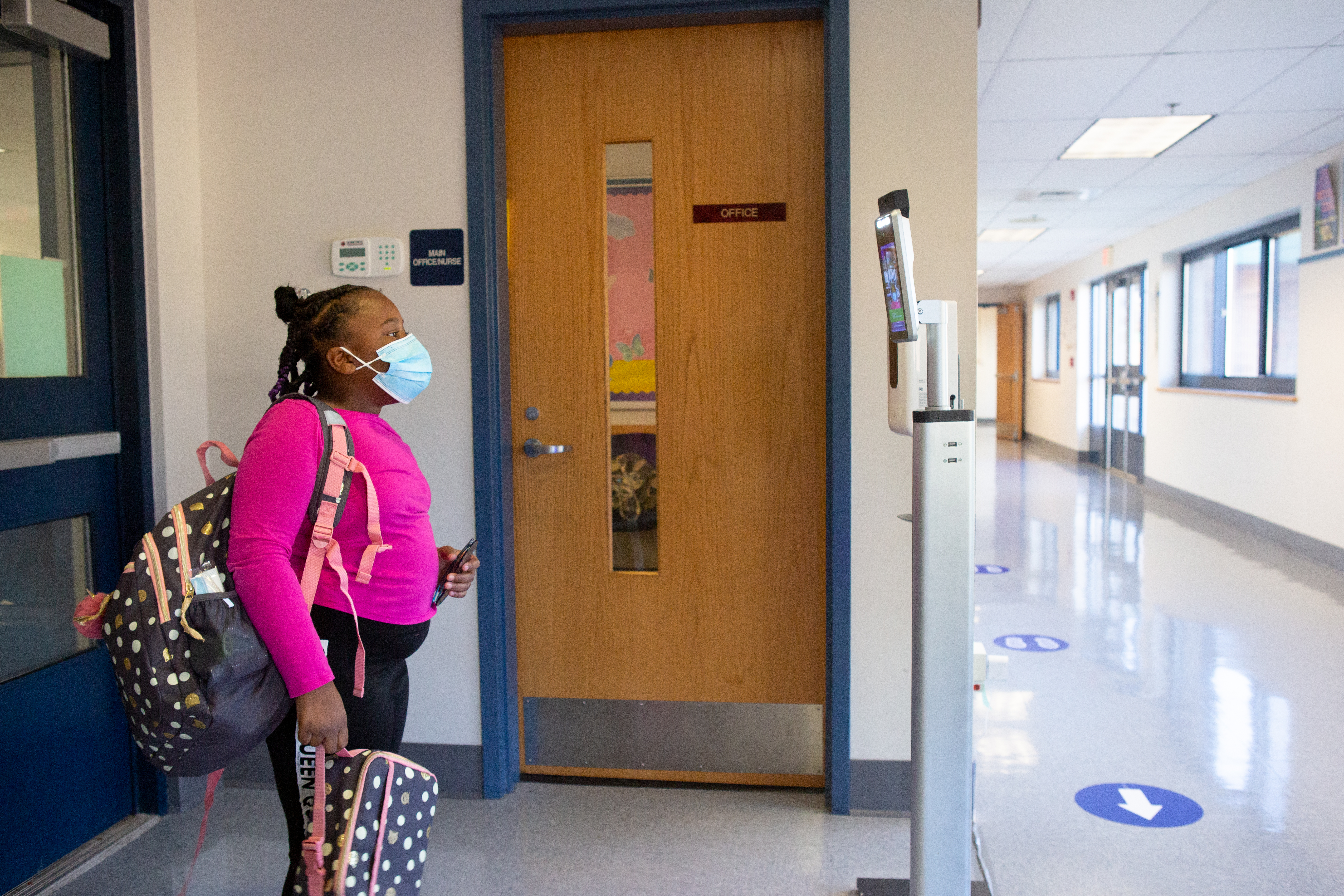 At student in a pink sweatshirt stands in front of a thermal temperature scanner at Wesley Elementary School in Middletown, CT, October 8, 2020.