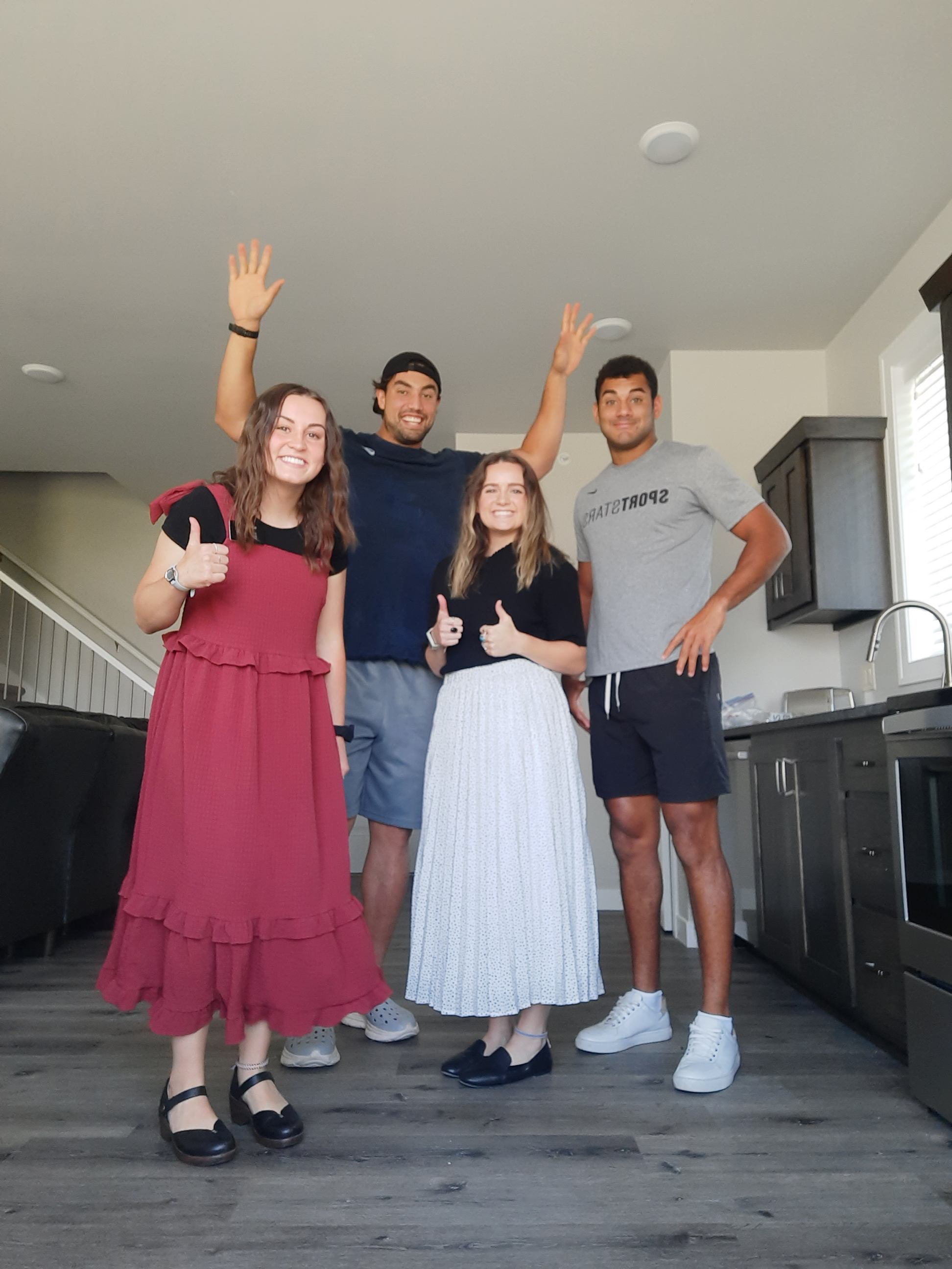Green Bay teammates Bronson Kaufusi (hands raised) and Christian Uphoff meet with Latter-day Saint sister missionaries.