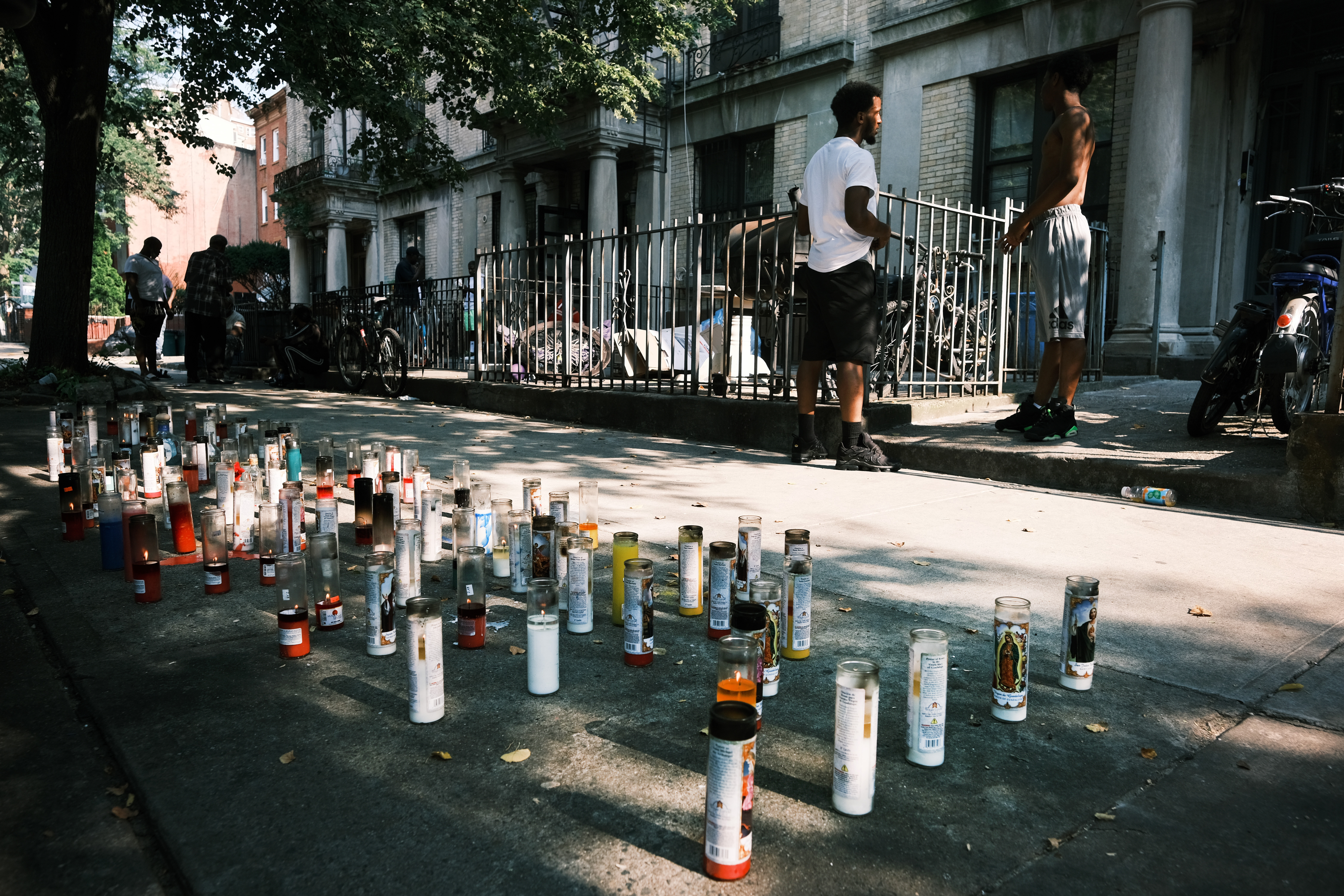 A memorial for a victim of gun violence sits on the edge of a sidewalk.
