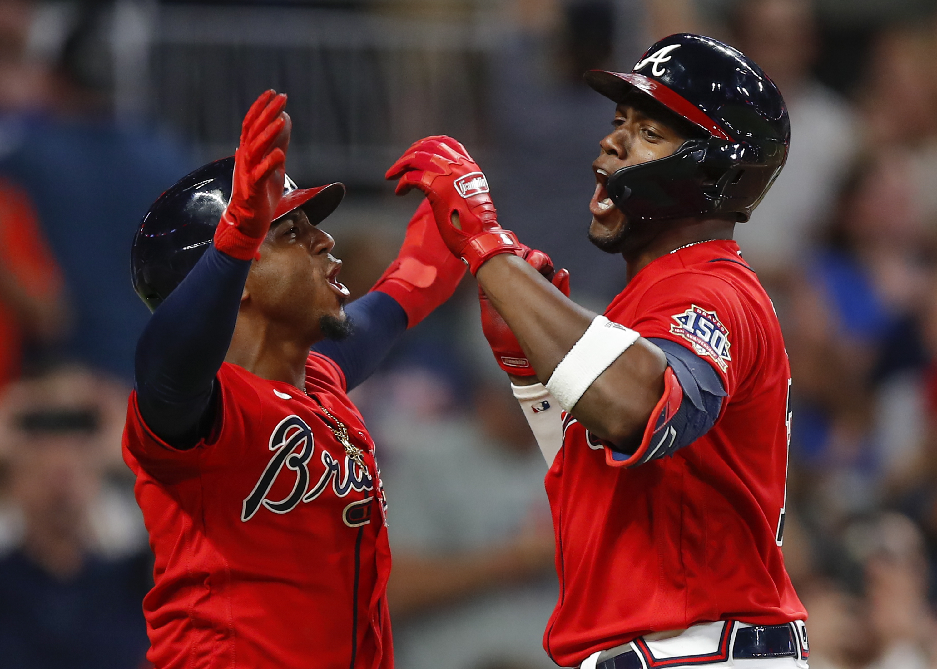 Jorge Soler of the Atlanta Braves reacts with Ozzie Albies after hitting a three-run home run in the seventh inning of an MLB game against the San Francisco Giants at Truist Park on August 27, 2021 in Atlanta, Georgia.