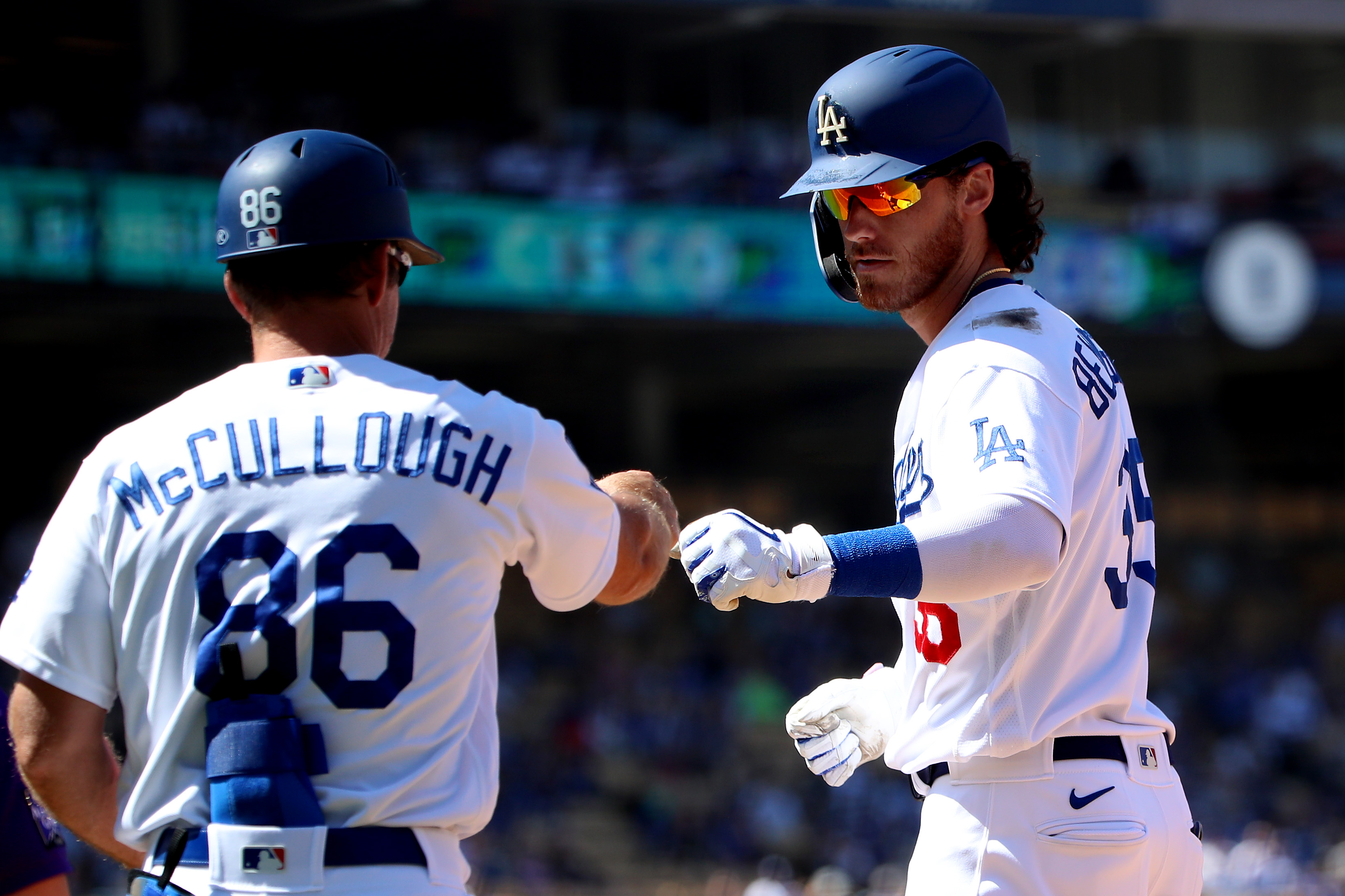 Cody Bellinger of the Los Angeles Dodgers celebrates his single with first base coach Clayton McCullough during the fifth inning against the Colorado Rockies at Dodger Stadium on August 29, 2021 in Los Angeles, California.