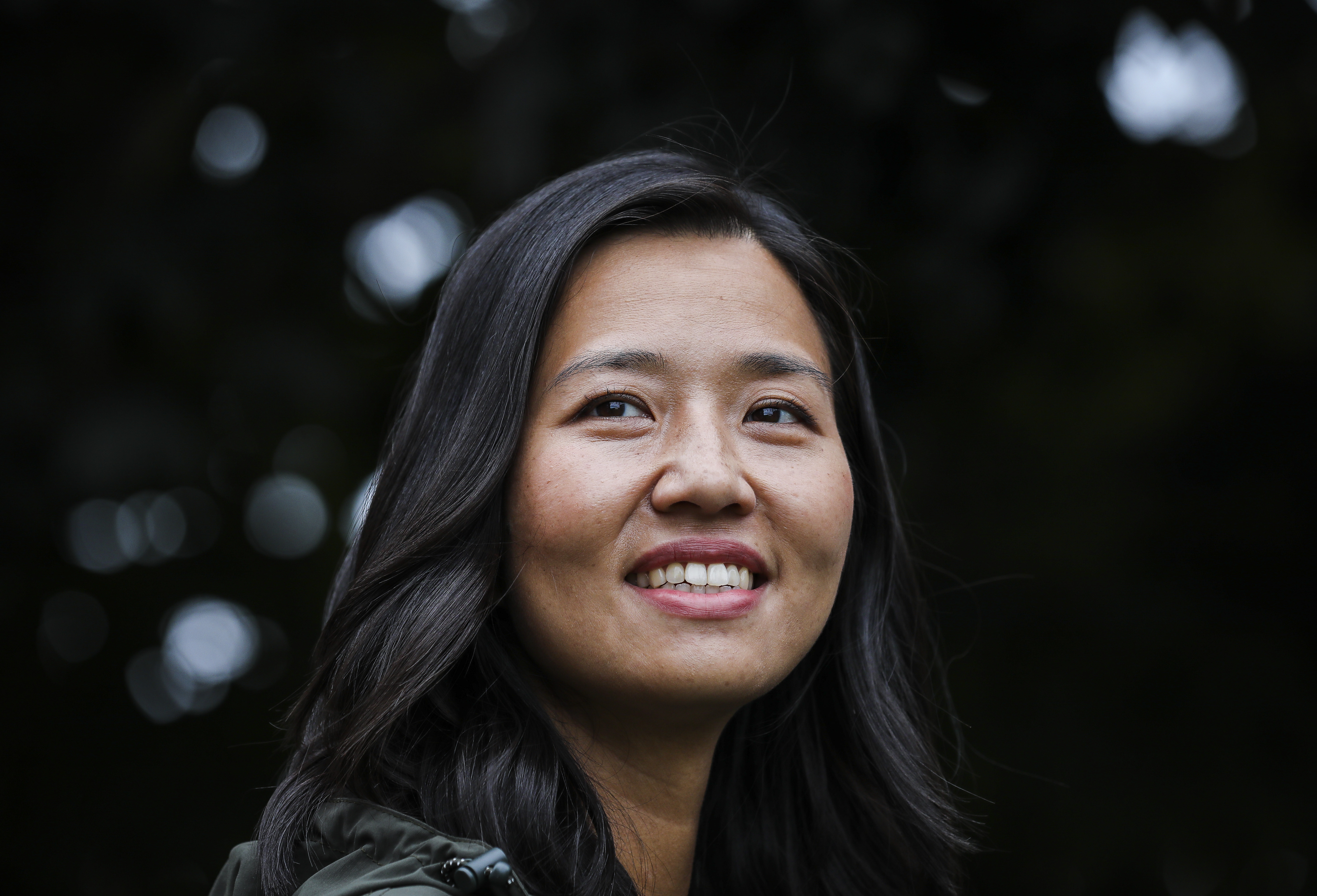 Closeup on a woman's smiling face in front of a dark background.