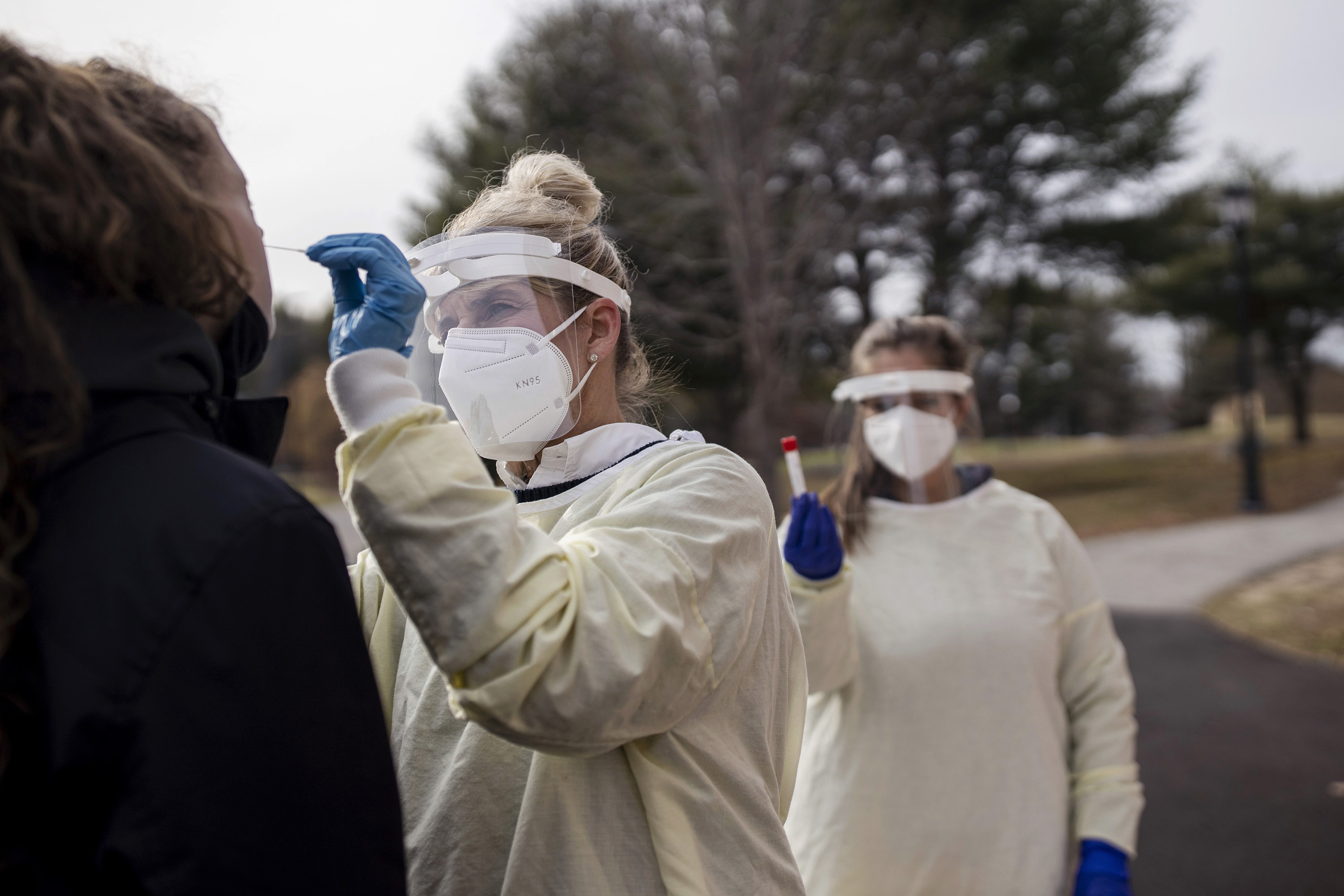 A health care worker in full mask, gown, gloves, and face shield performs a Covid-19 test swab outdoors on a student heading to school.