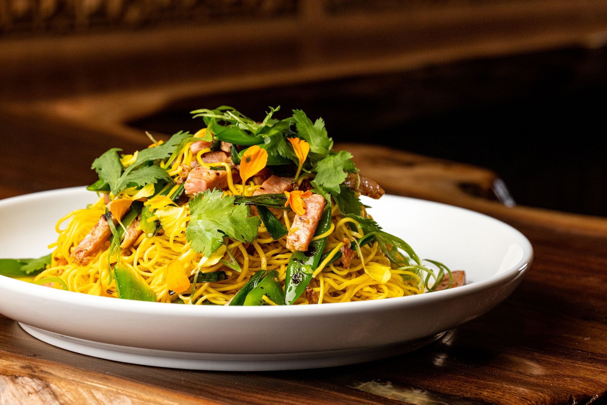 a plate of noodles topped with shredded ham and cilantro
