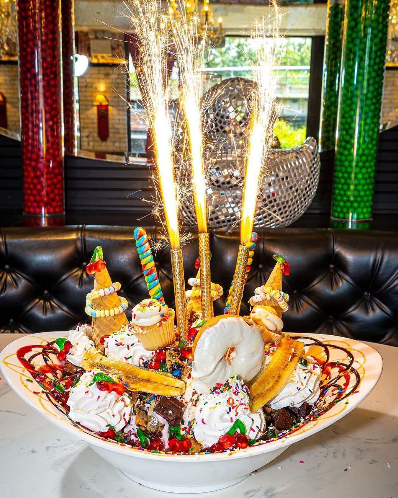 An outrageous ice cream sundae with sparklers on top