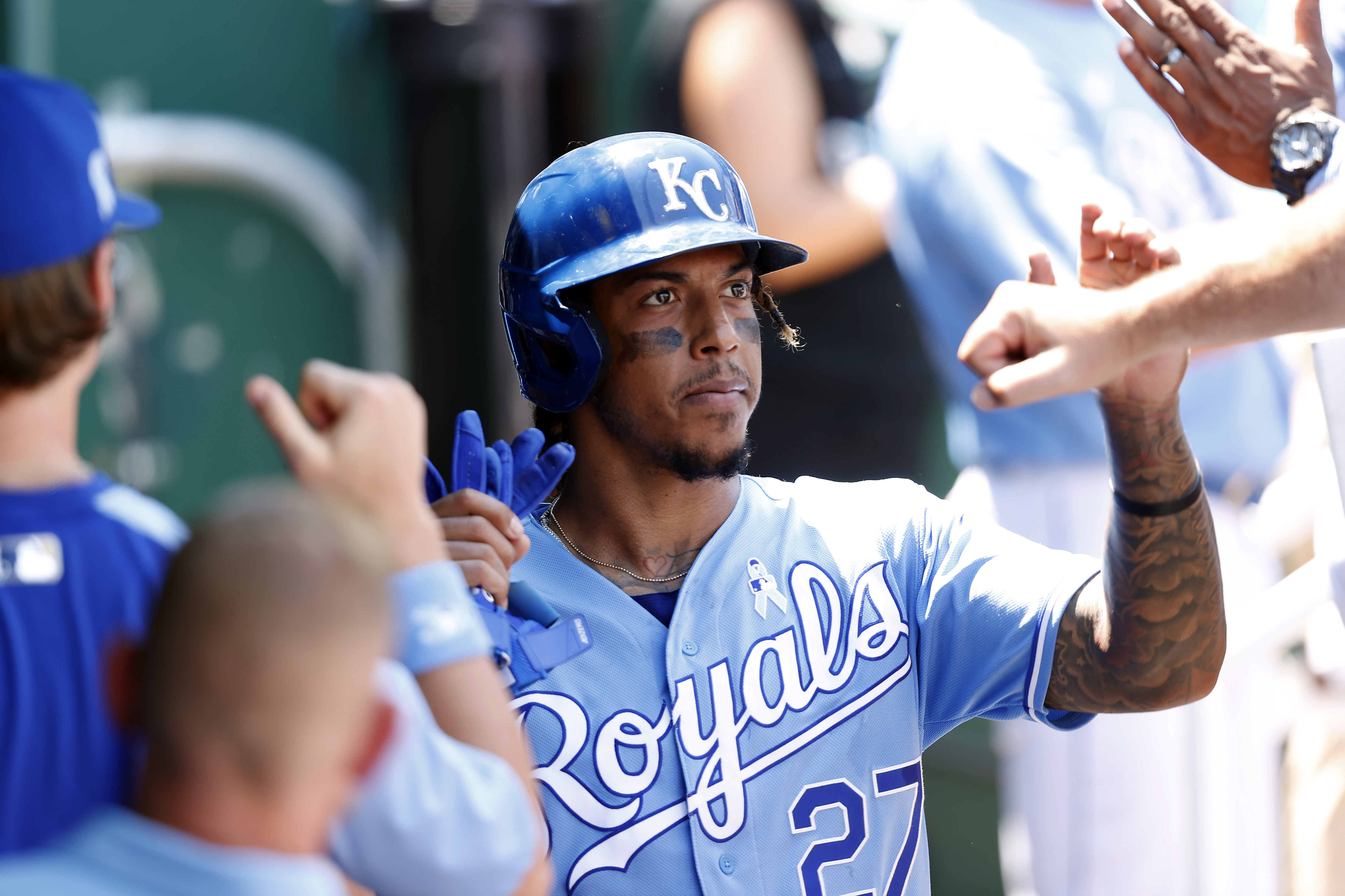 Adalberto Mondesi #27 of the Kansas City Royals is congratulated by teammates in the dugout after scoring during the 3rd inning of the game against the Boston Red Sox at Kauffman Stadium on June 20, 2021 in Kansas City, Missouri.