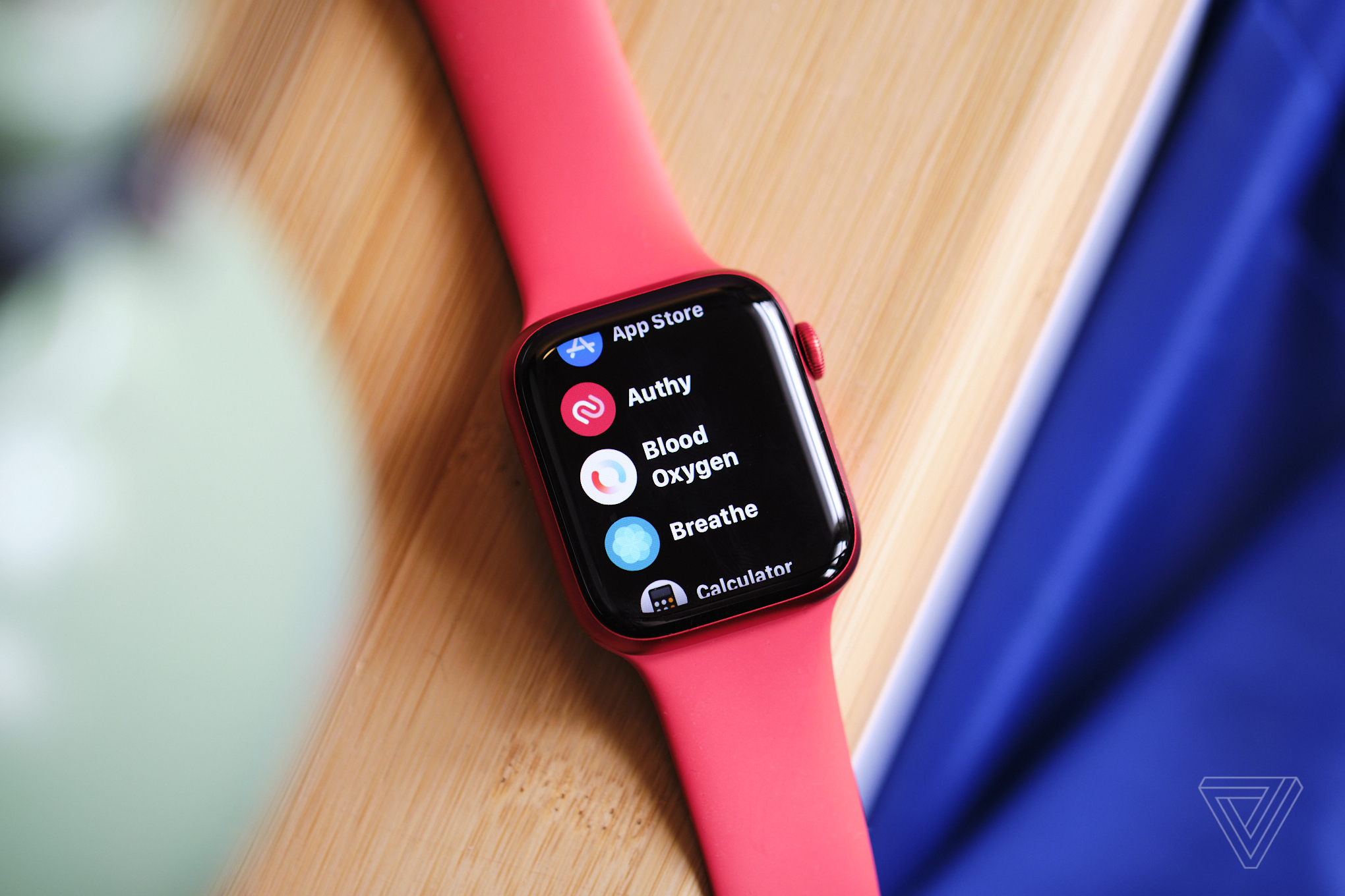 An Apple Watch with a red wristband sitting on a table, showing the blood oxygen app.