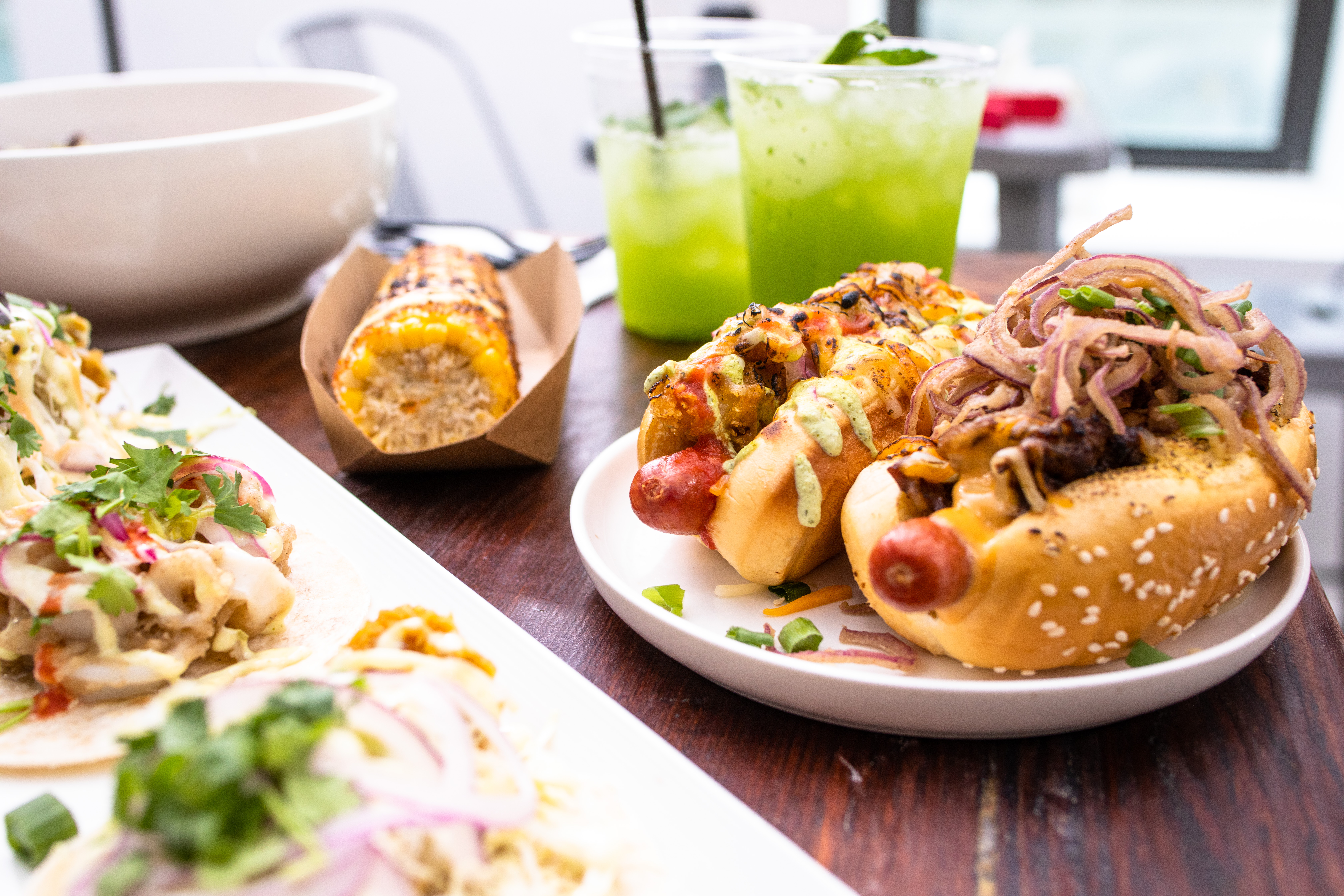 two loaded hot dogs with elote corn and margaritas
