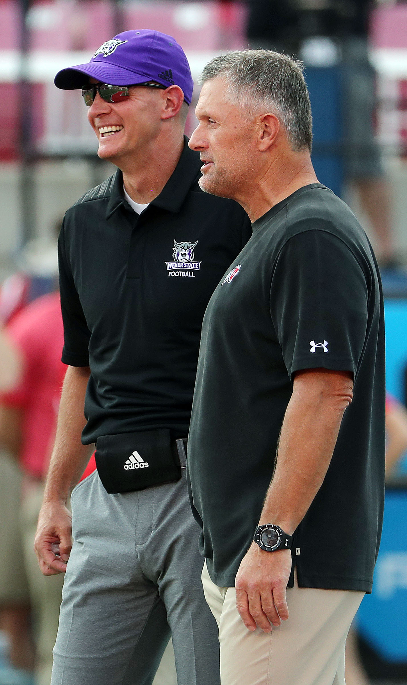 Utah Utes coach Kyle Whittingham, right, and Weber State Wildcats coach Jay Hill talk before game in Salt Lake City.