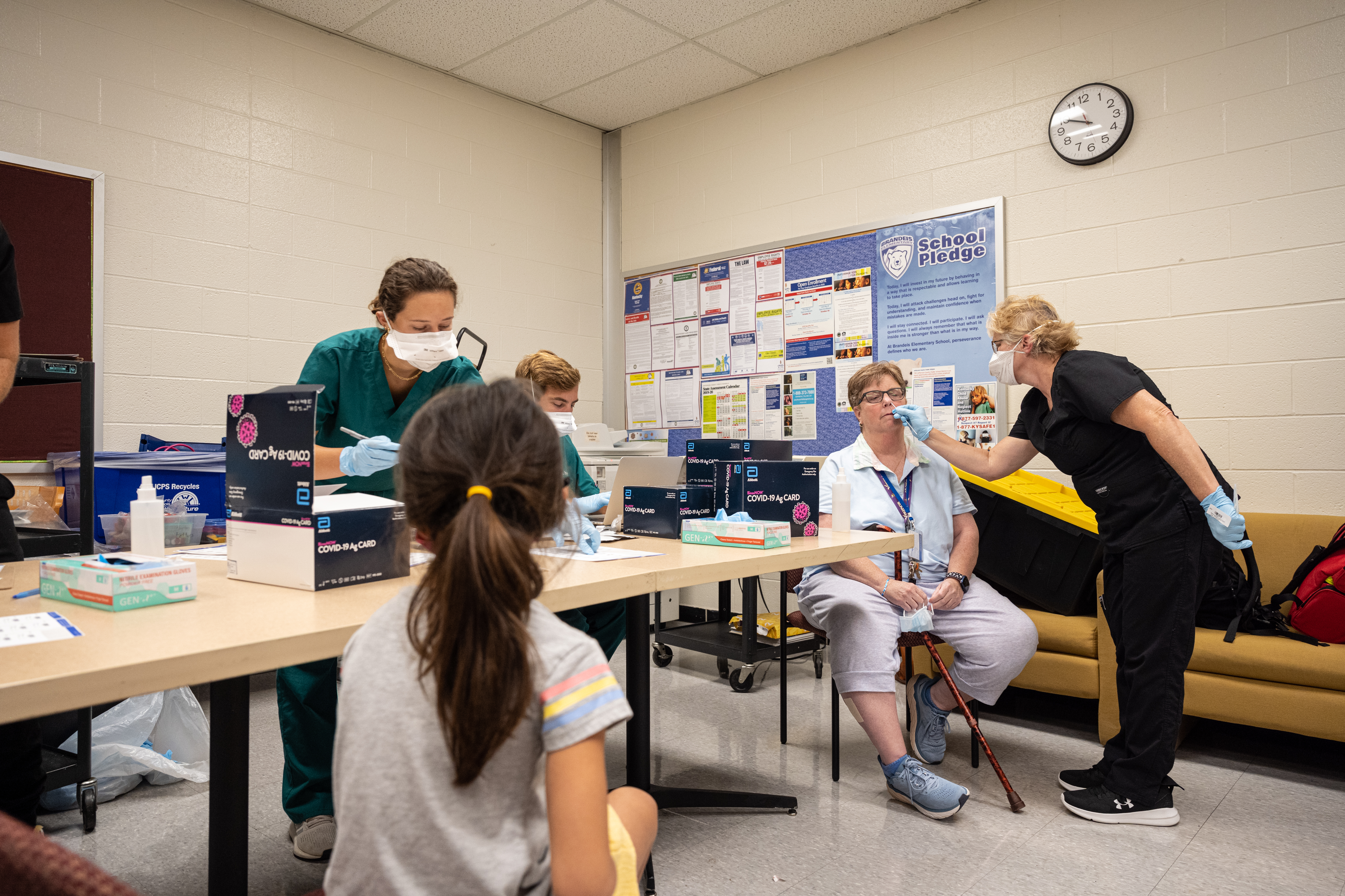 Health care professionals conduct COVID testing in an office with white brick walls.