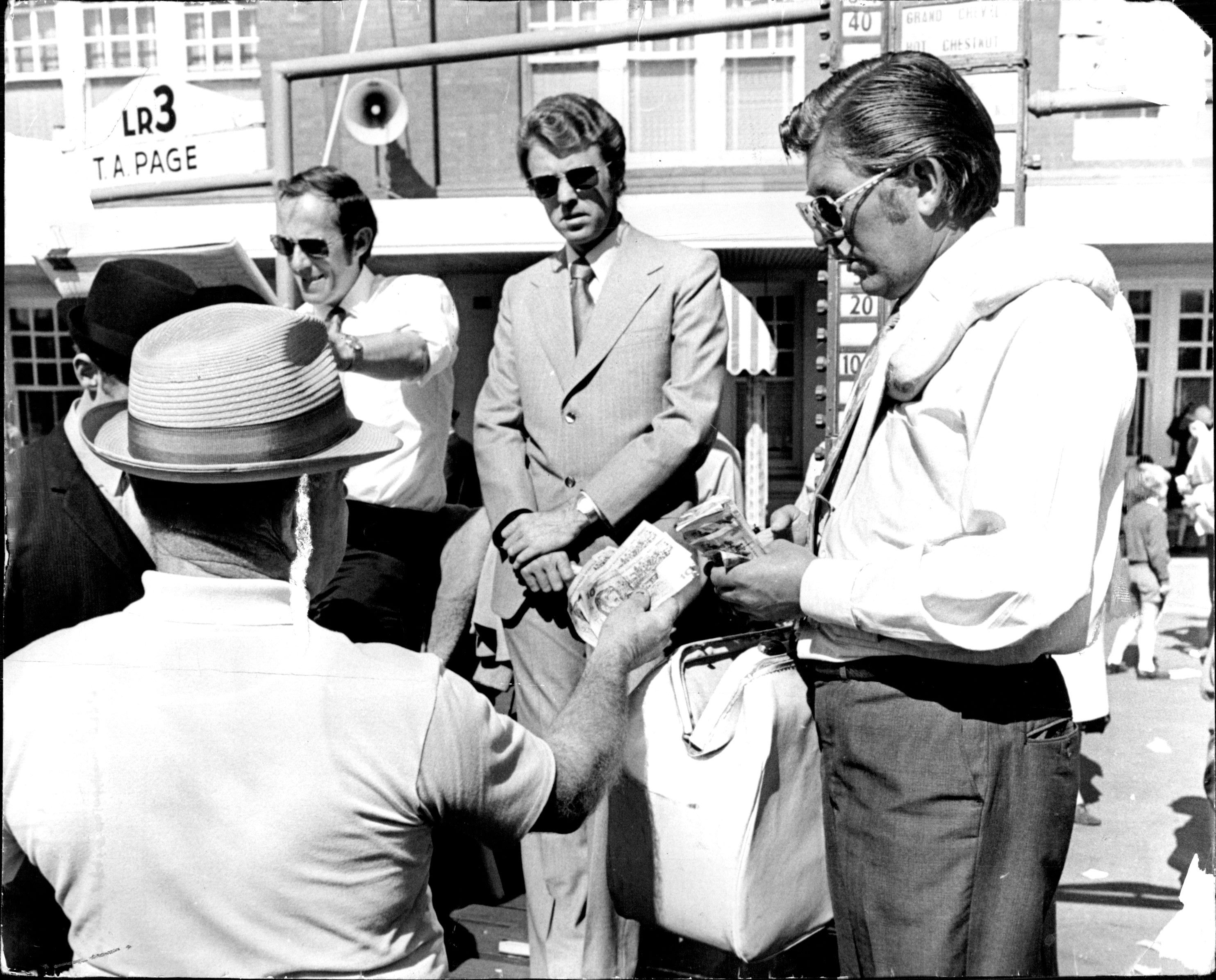 """Bookmaker Terry """"Mister Money"""" Page (centre) looks on as a punter moves in to make a bet with his bagman.To Go With Special Bookmaking Series For Sun Special - Punters shown laying odds with bookmakers at Randwick Racecourse this afternoon."""