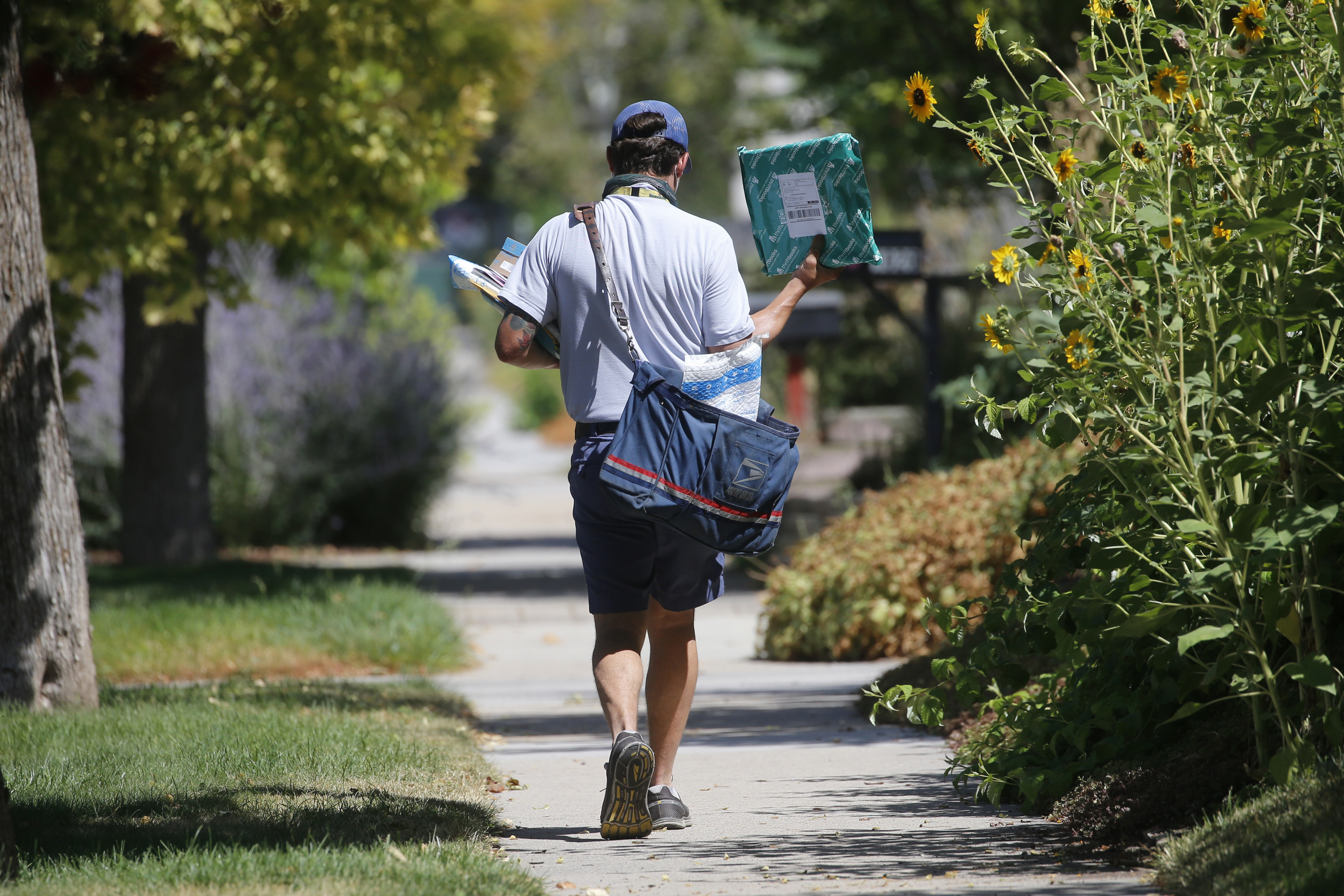 A U.S. Postal Service carrier delivers mail to homes in Salt Lake City, Utah. The Postal Service regularly cheats mail carriers out of their pay, a Center for Public Integrity investigation finds.