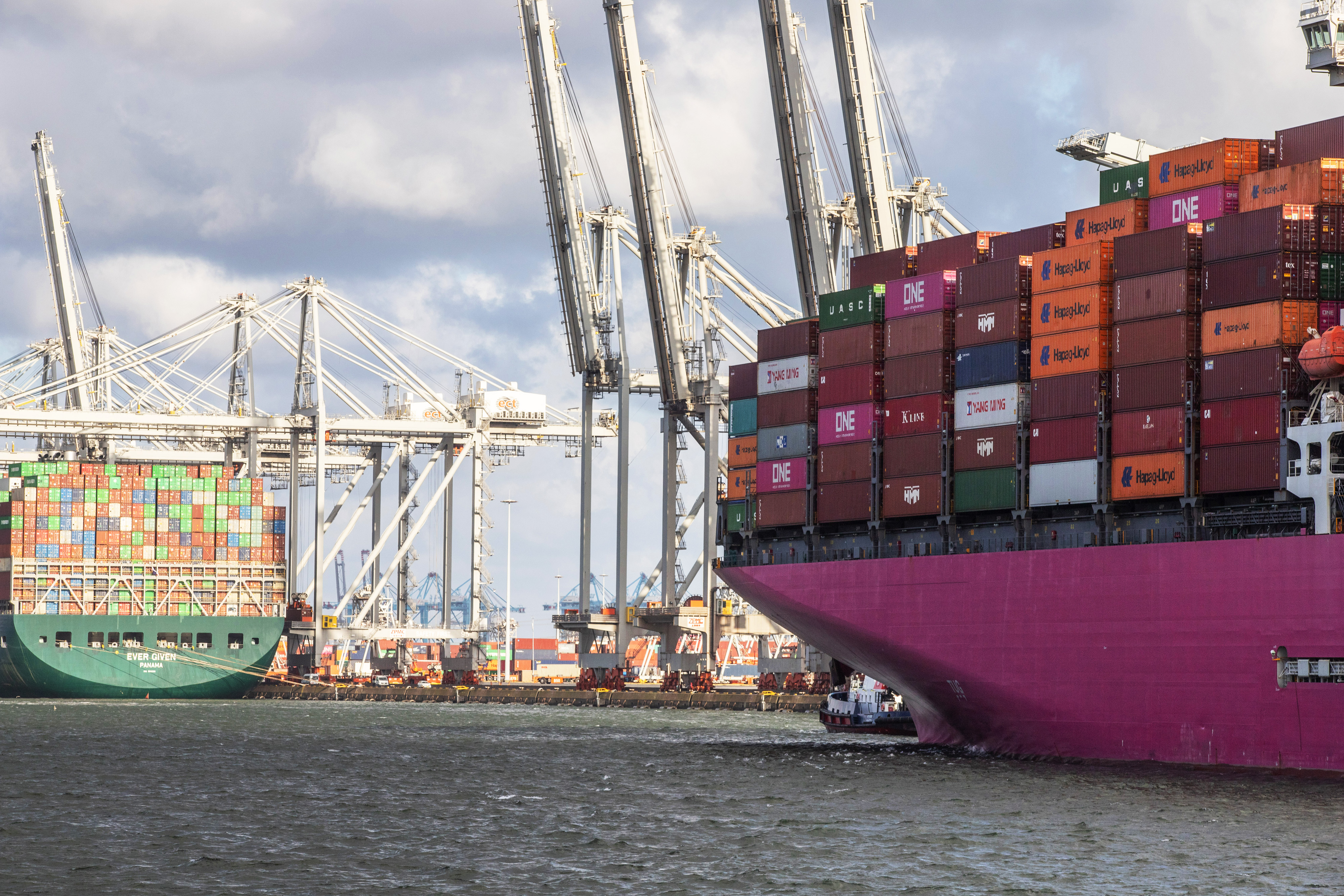 A container ship docked near the One Ibis cargo vessel at a port in Rotterdam, Netherlands.