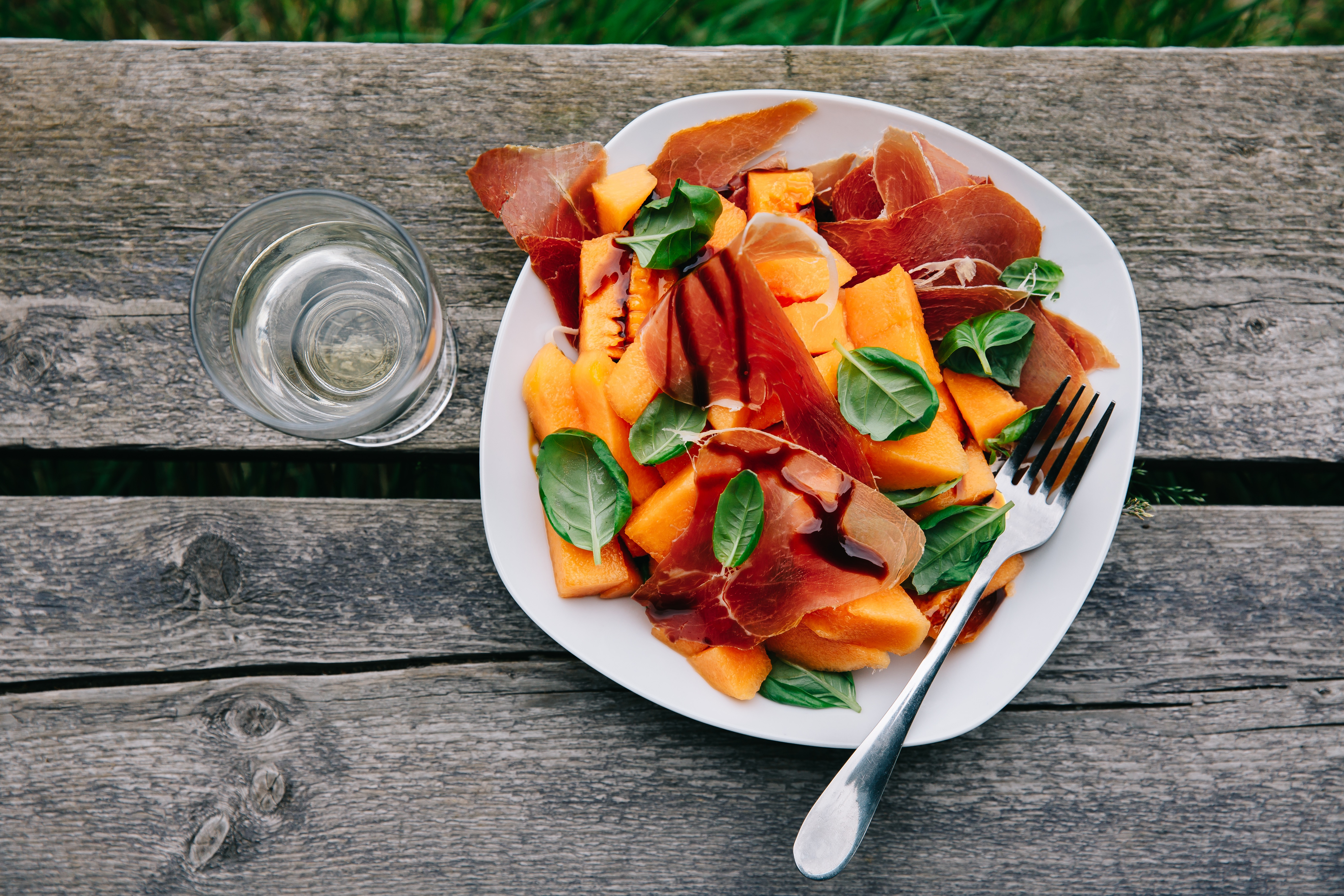 An overhead shot of a melon and prosciutto salad on a wooden picnic table.