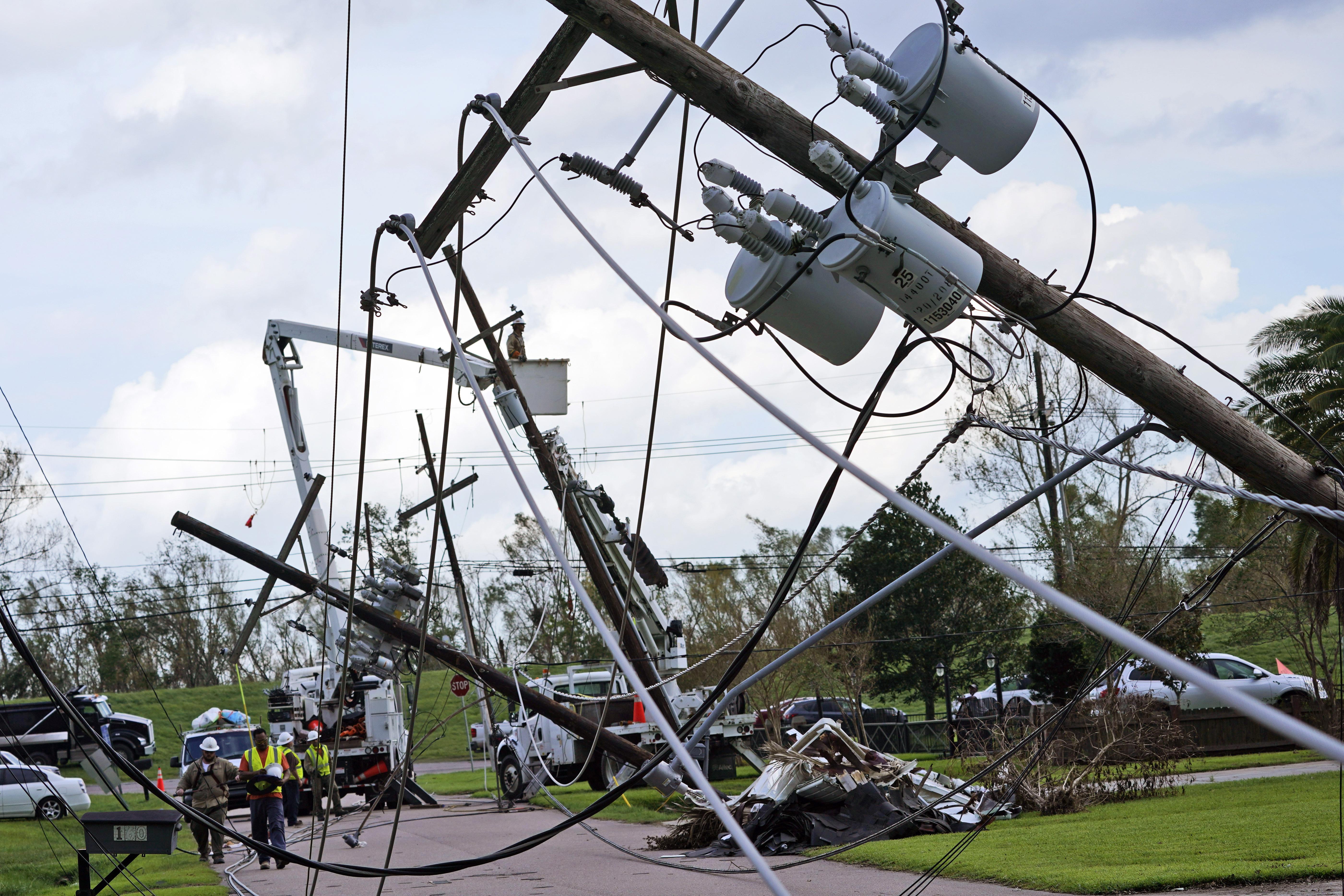 Crews repair a series of downed power lines after Hurricane Ida.