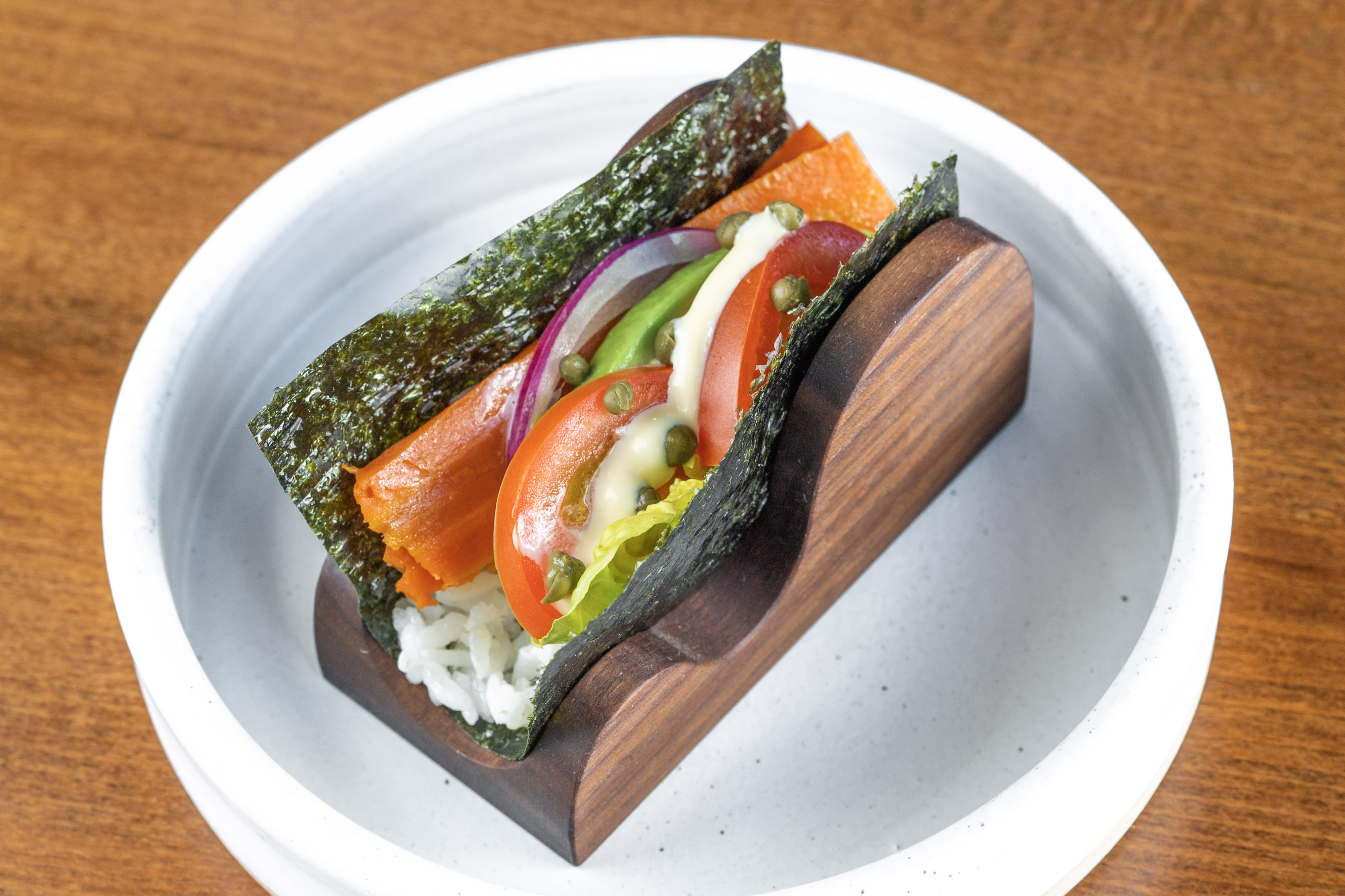 """A vegetarian handroll filled with cured carrot """"lox,"""" tomato, red onion, capers, and rice"""