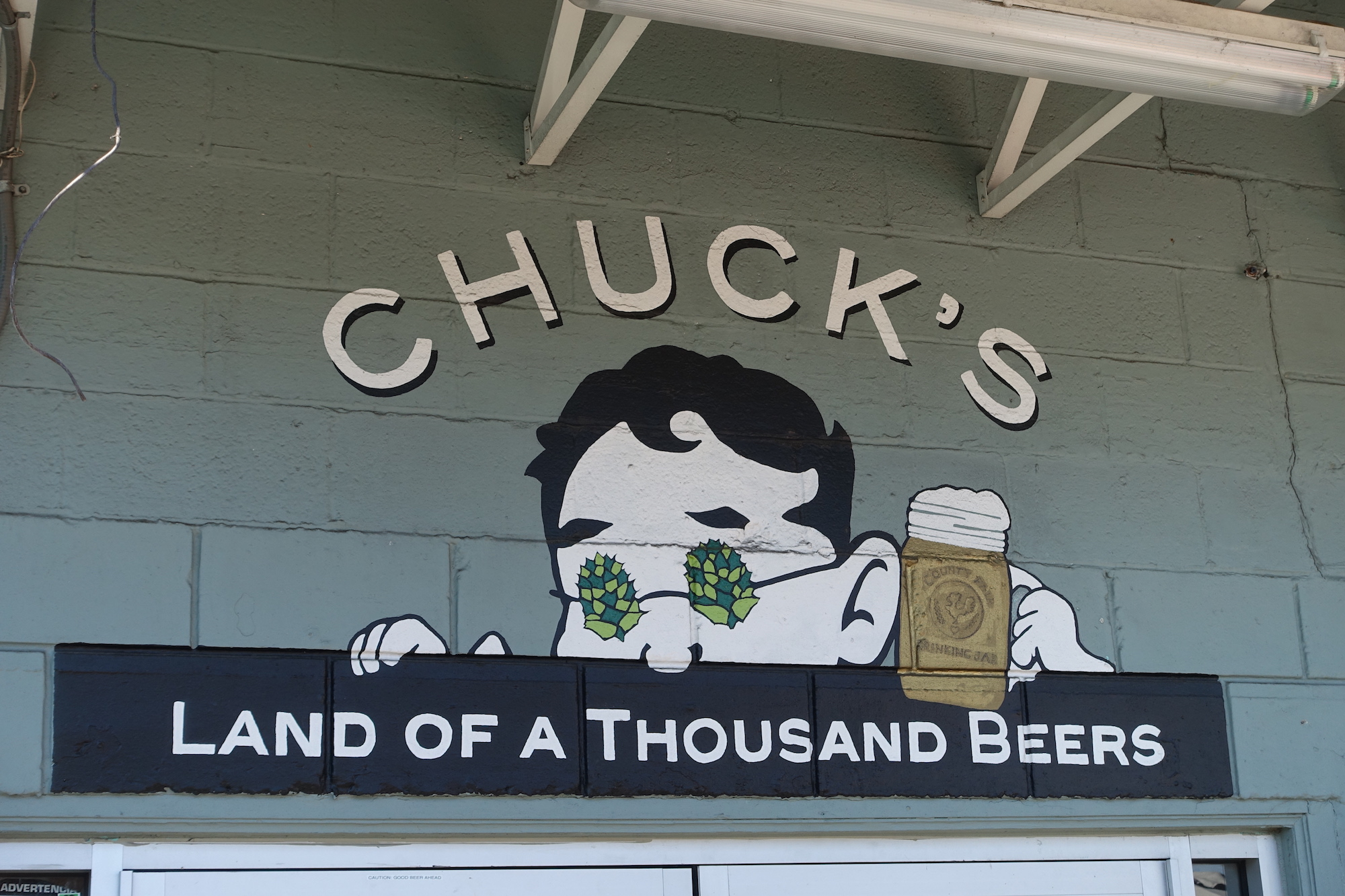 """The mural at Chuck's Hop Shop which has a drawing of a man wearing glasses with hops on them while holding a beer; below it says """"Land of a Thousand Beers"""""""