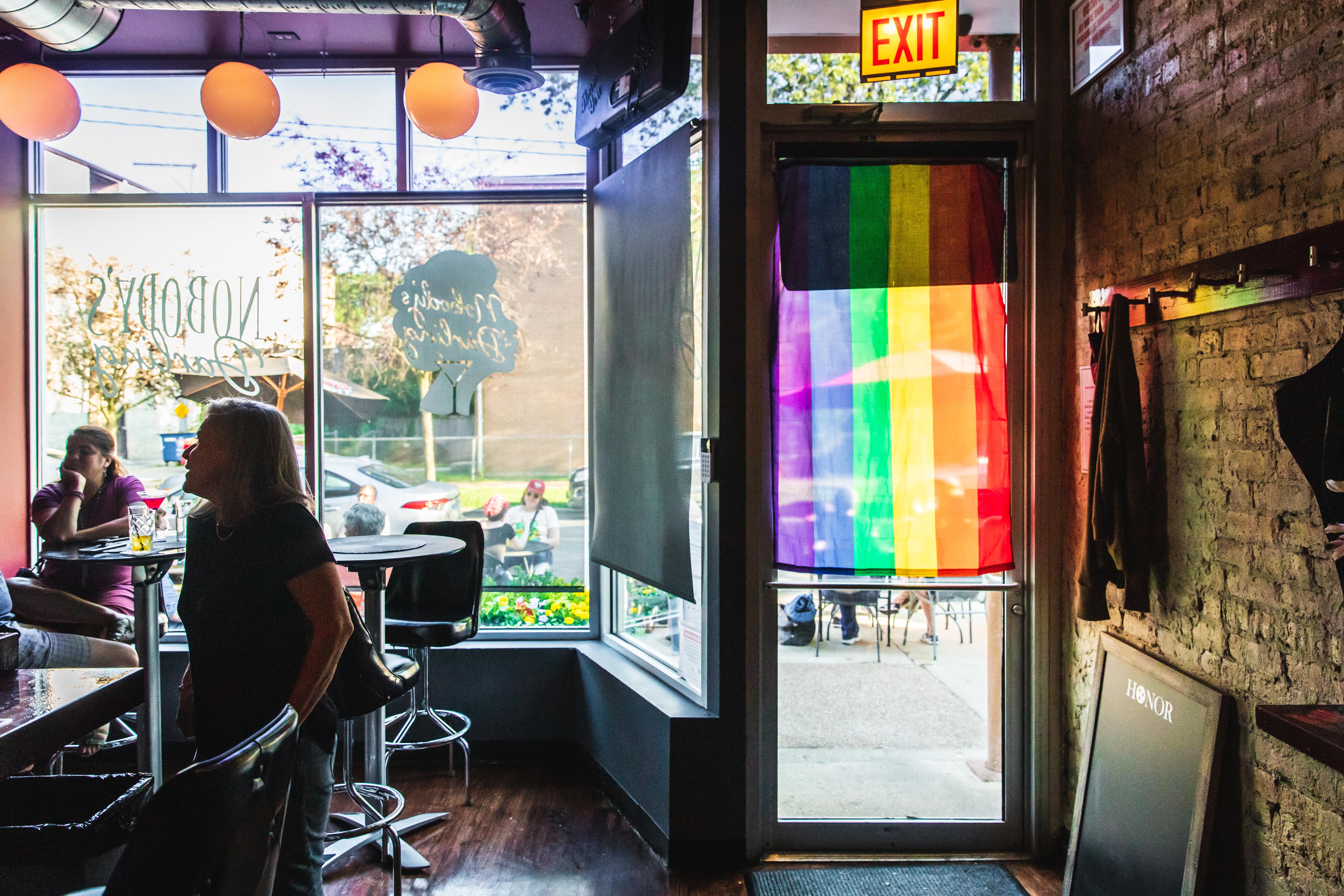 A rainbow flag hangs over the glass door of a narrow bar